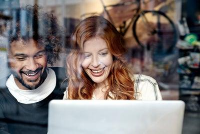 Deux jeunes gens regardent un ordinateur portable en riant.