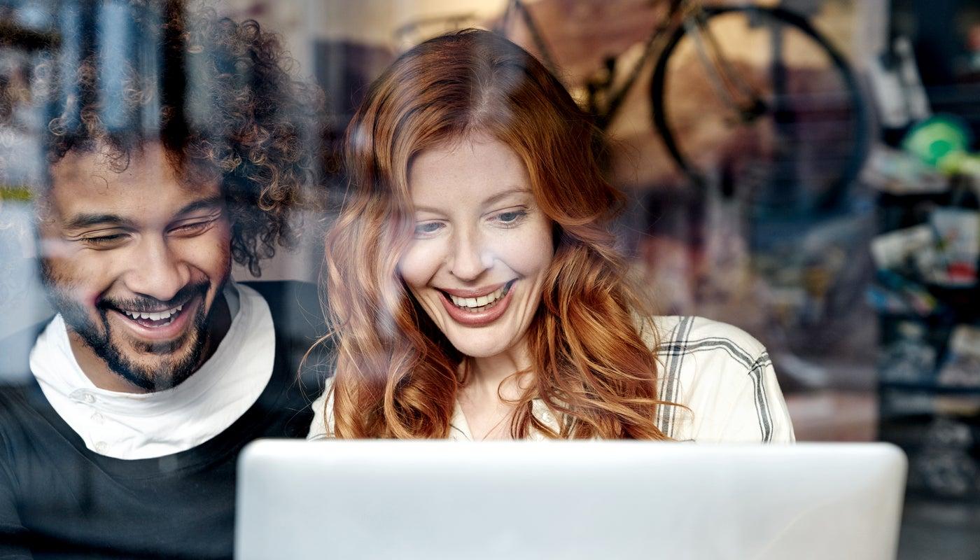 Zwei junge Personen schauen lachend auf einen Laptop.
