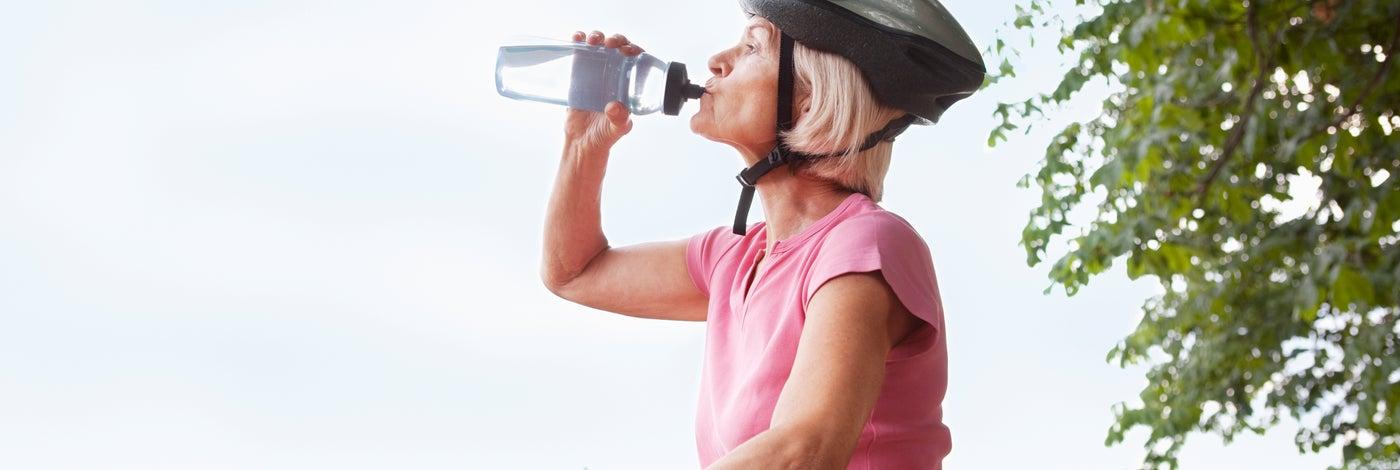 Femme à vélo buvant de l'eau