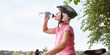 Frau auf Fahrrad trinkt Wasser