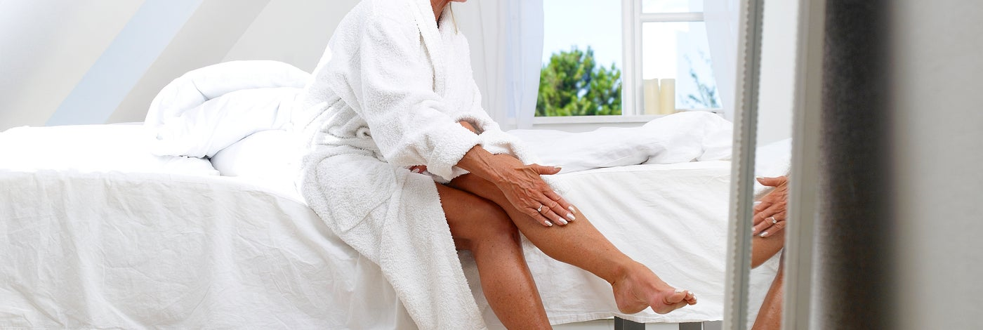 Une femme se met de la crème à les jambes