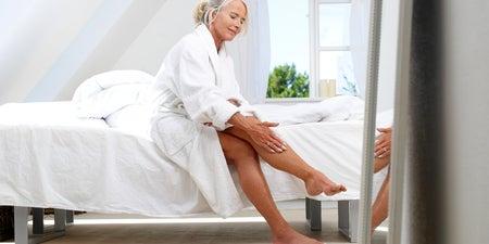 Frau cremt sich die Beine ein