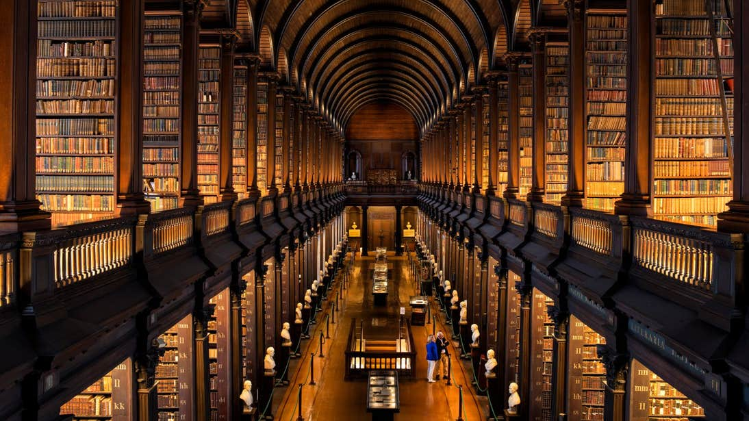 Books and marble busts of famous writers lining the walls in the Long Room at Trinity College, Co. Dublin