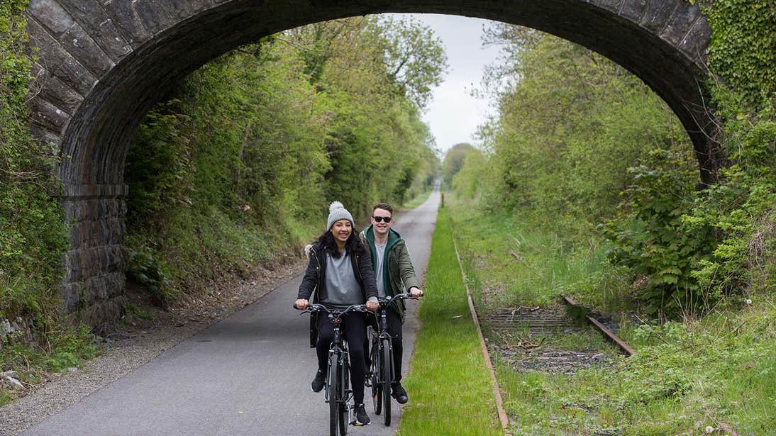 Two people cycling on Old Rail Trail Greenway Athlone Westmeath under a bridge