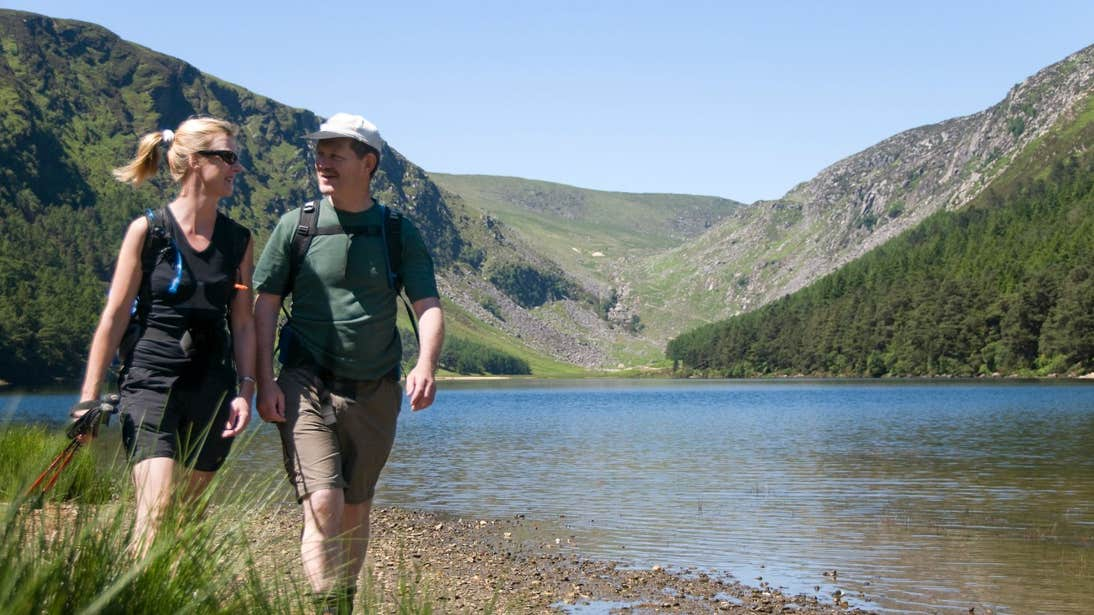 Two people walking beside a lake in Glendalough, Wicklow Mountains National Park, County Wicklow
