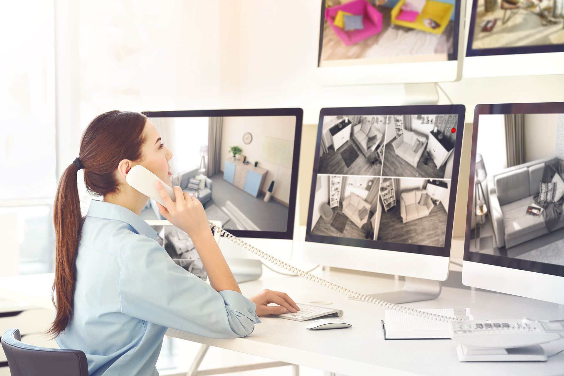 жена проверява няколко монитора с видеонаблюдение с камери