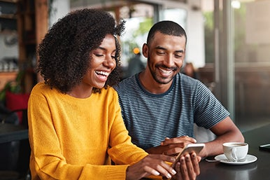 Two tax students smiling while looking at a mobile device, and having coffee.