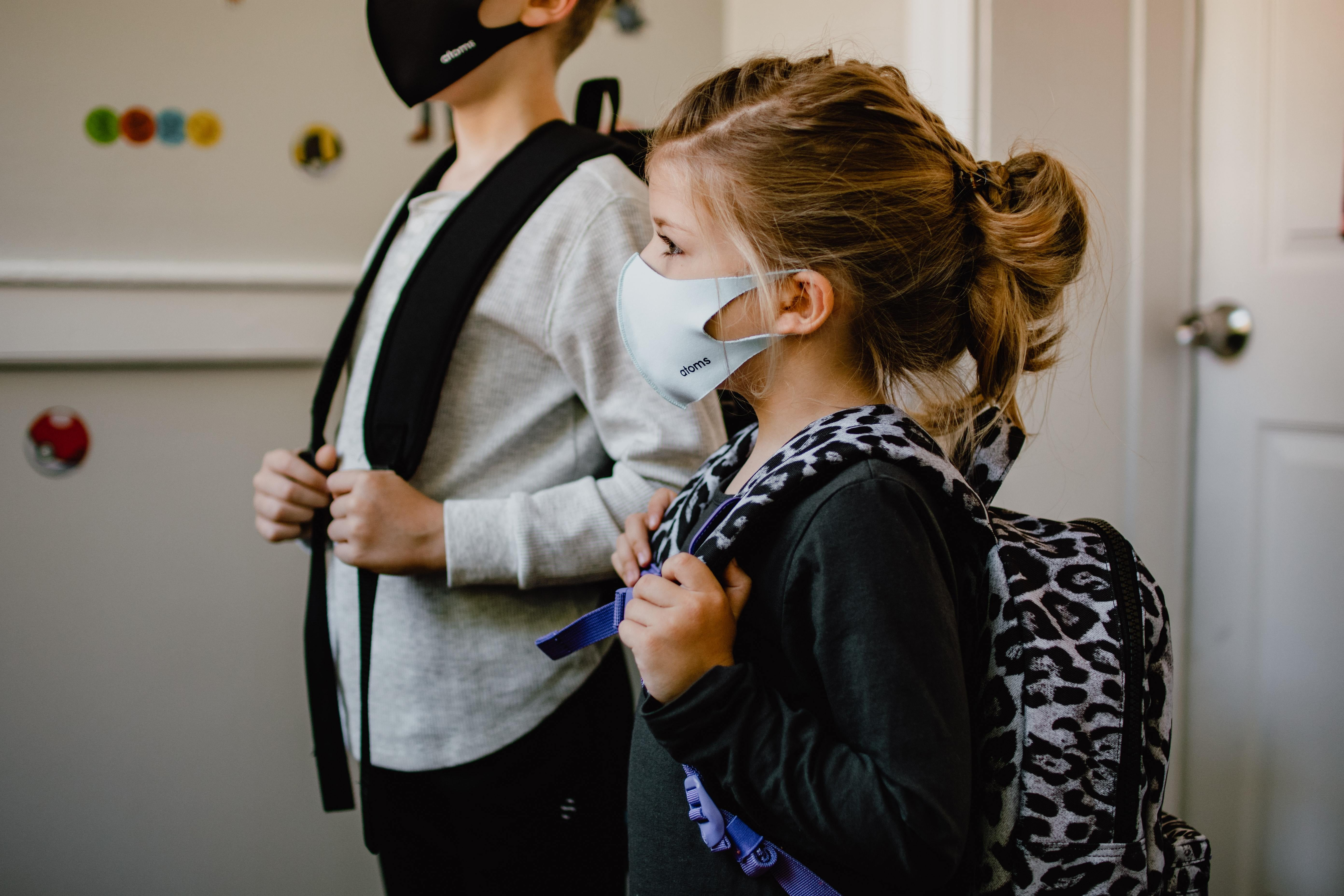 Two children wearing their masks with their school bags on