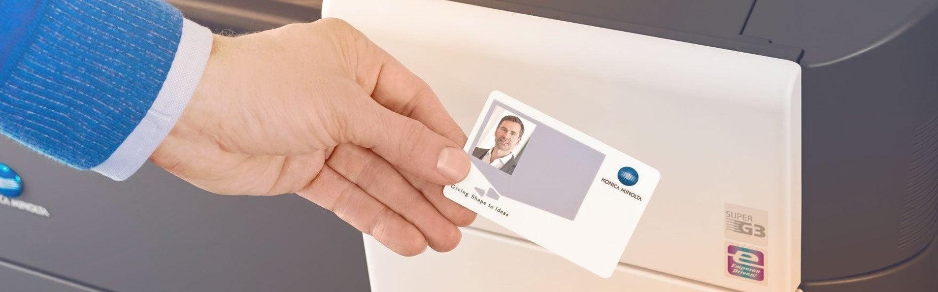 Mann hält Ausweis vor Drucker