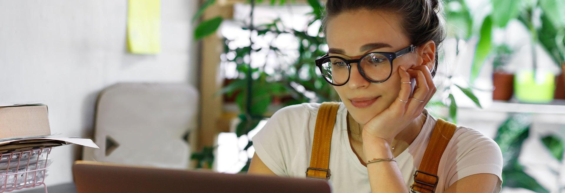 Nahaufnahme einer Frau, die in ihrem Homeoffice vor dem Laptop sitzt, im Hintergrund ein paar Pflanzen und Unterlagen