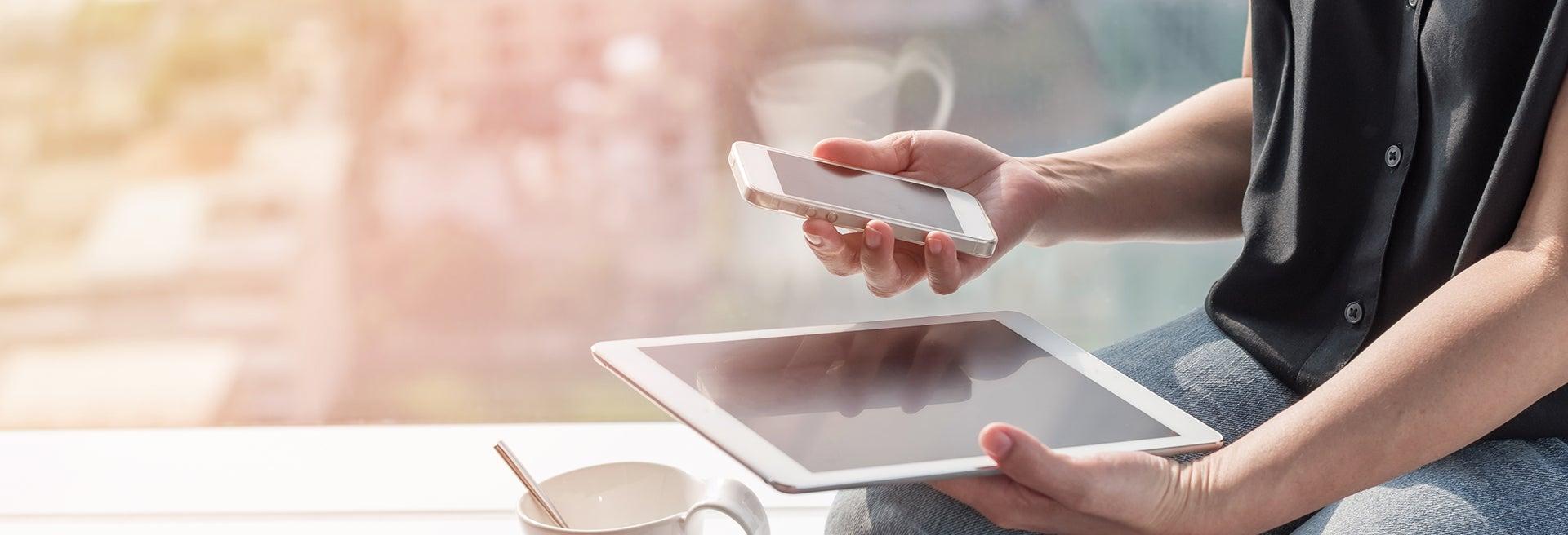 Frau sitzt auf einem Schreibtisch und hält ein Smartphone sowie Tablet in der Hand