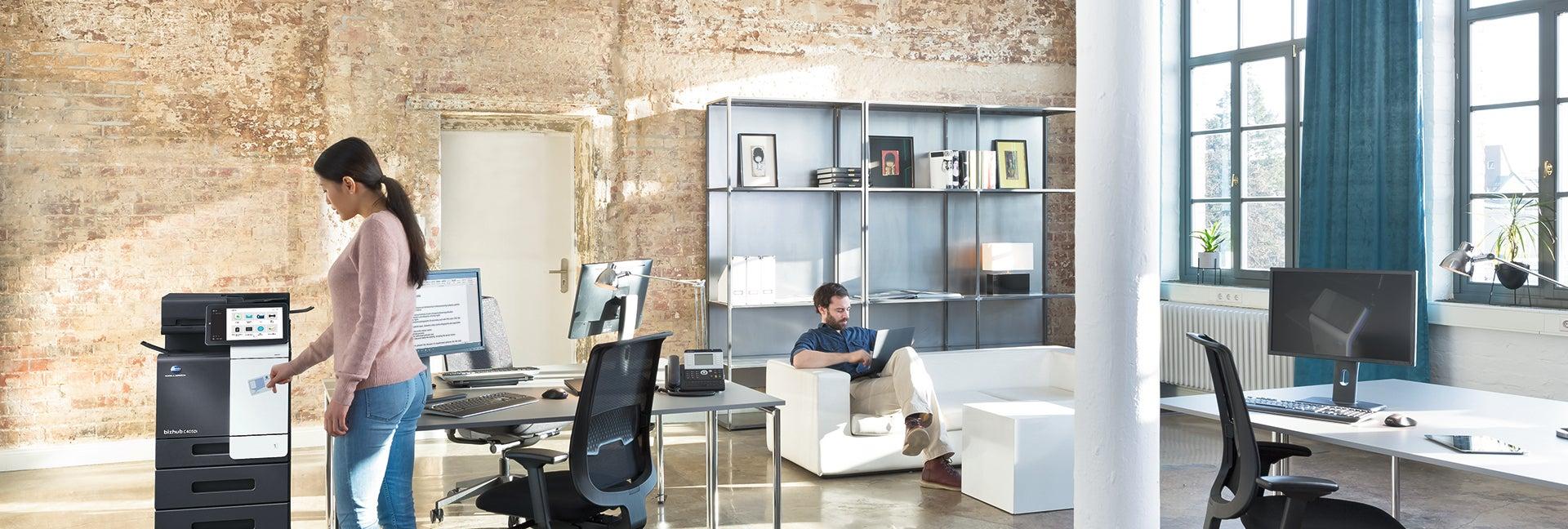 Frau steht vor dem Bürodrucker und holt einen Ausdruck aus dem Ausgabefach im Hintergrund ein Kollege, der auf der Couch sitzt und am Laptop arbeitet