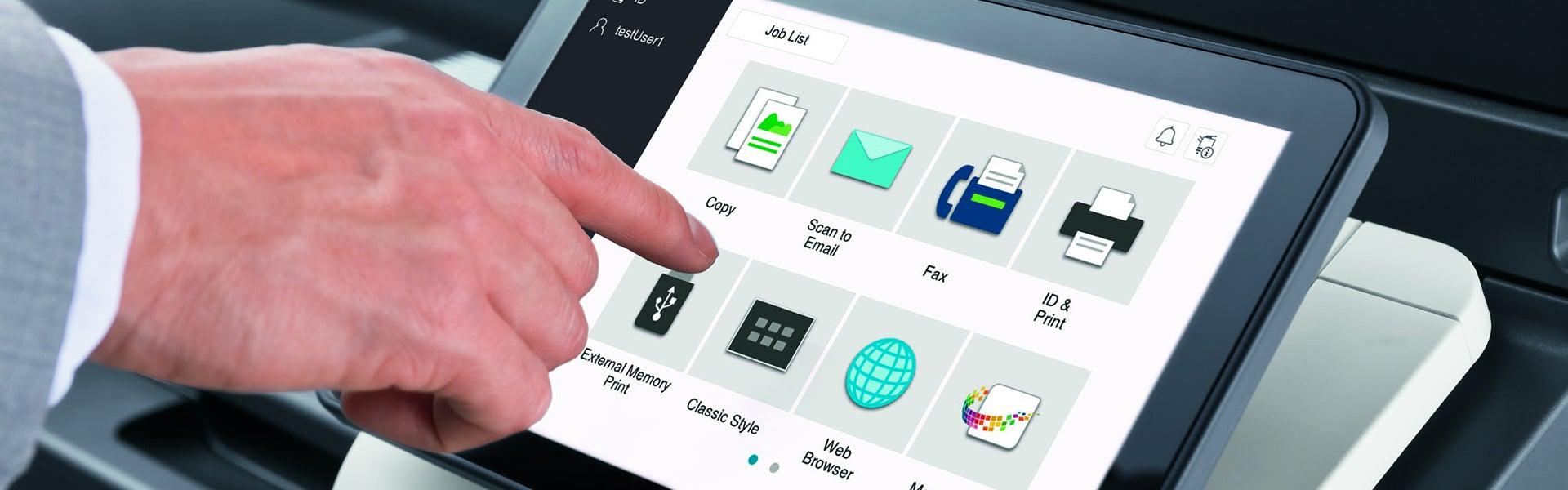 Großaufnahme einer Hand, die den Touchscreen eines Multifunktionssystems zum Drucken, Scannen und Kopieren bedient