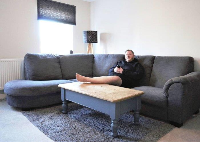 Image of Luke sat on his sofa in his new shared ownership home