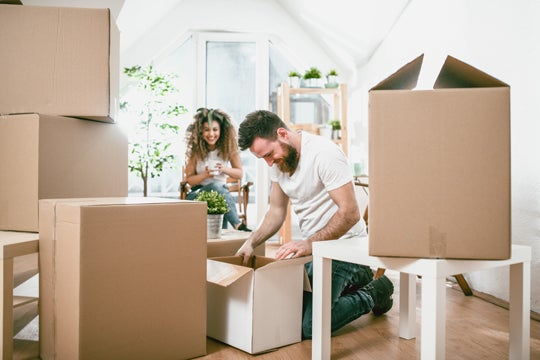 Man and woman unpacking boxes in new house