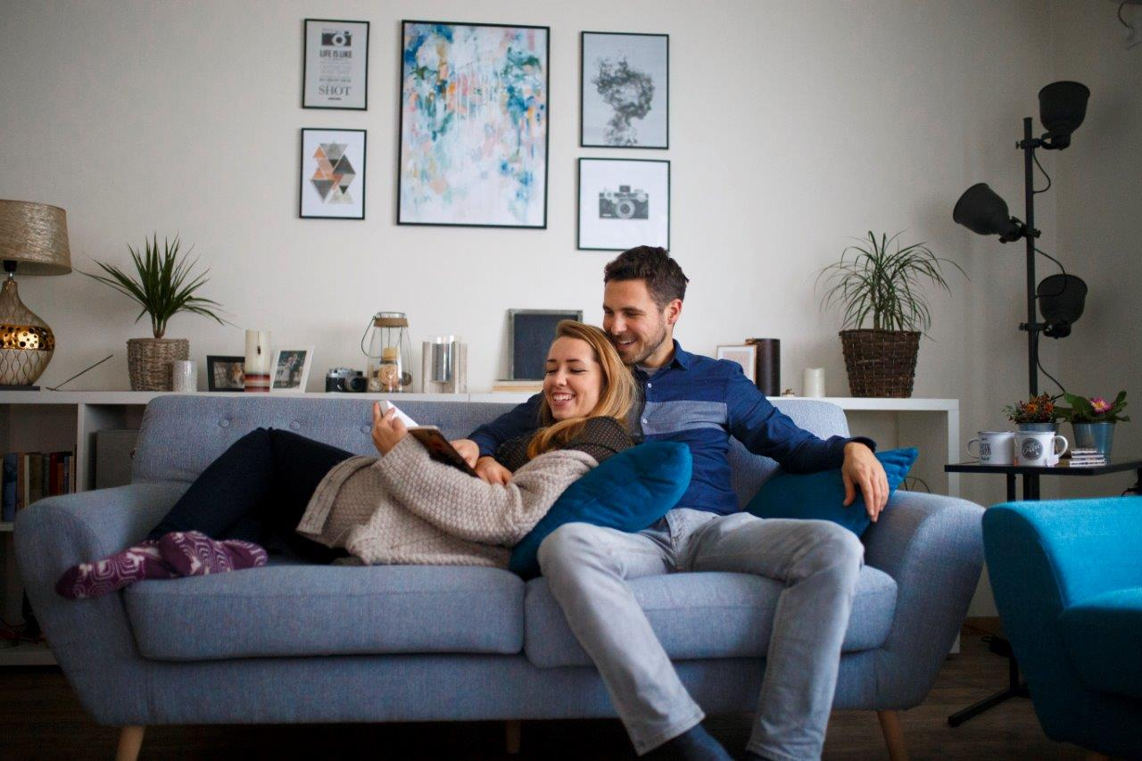 couple relaxing on their sofa at home