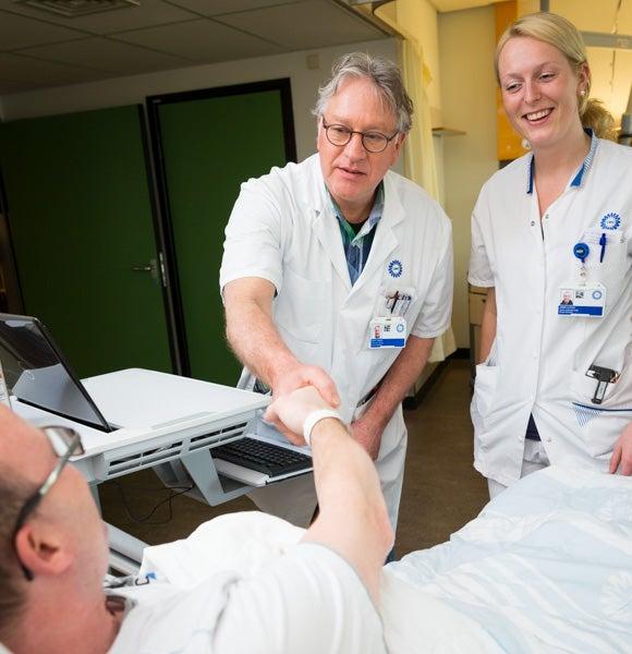 Arts en verpleegkundige aan het bed bij een patiënt