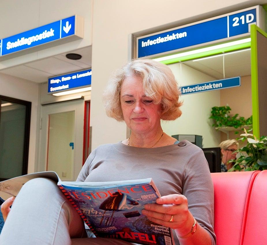 Vrouw leest tijdschrift in de wachtruimte