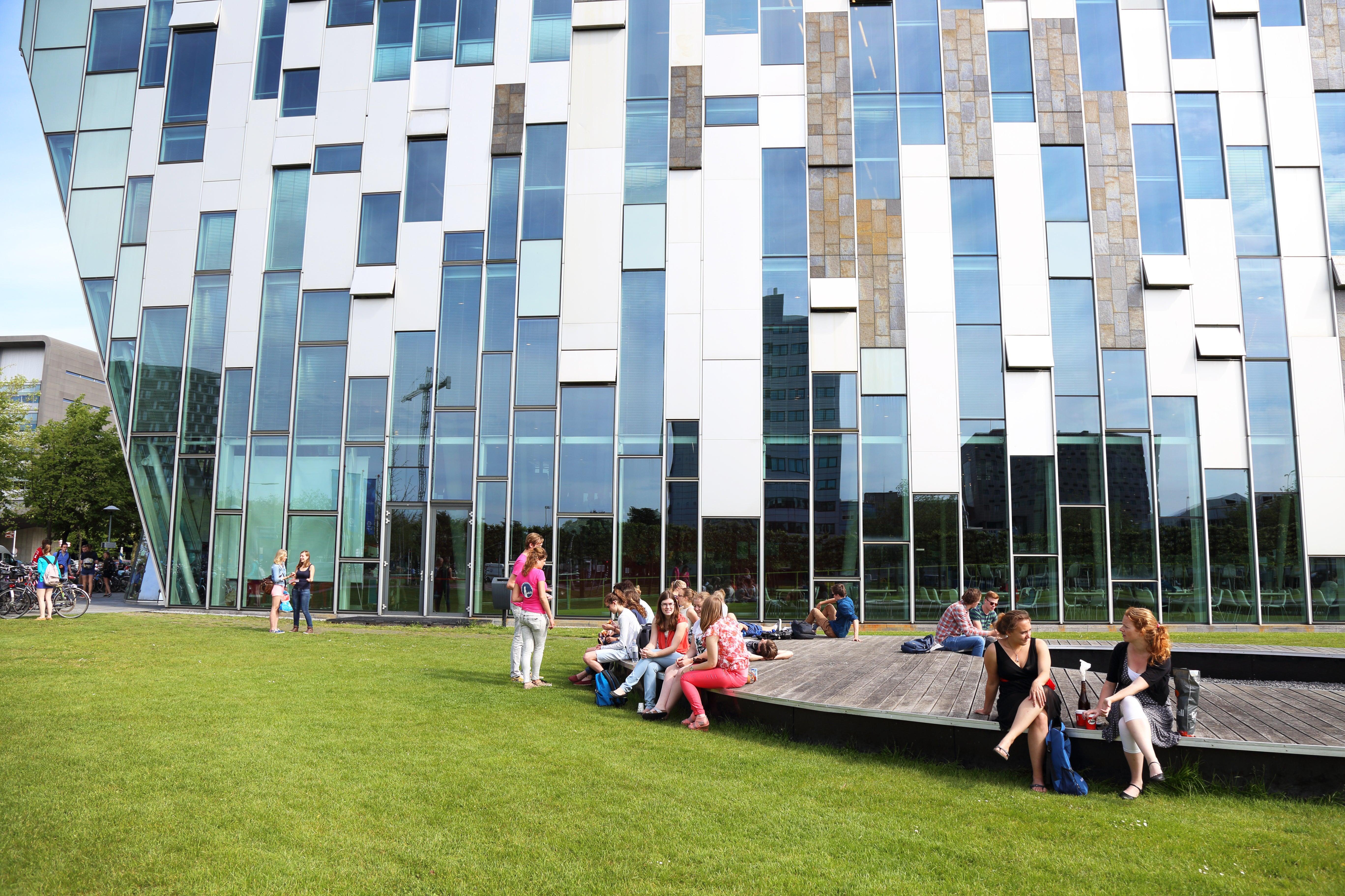 Gebouw van de geneeskunde opleiding, op voorgrond zitten studenten op terras