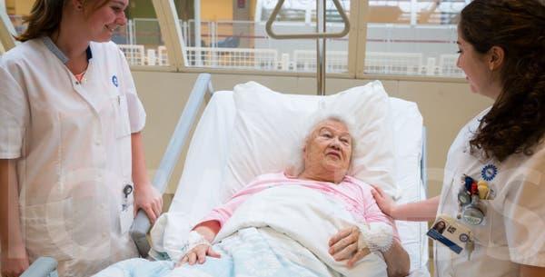 Oude vrouw in ziekenhuisbed met verpleegkundigen