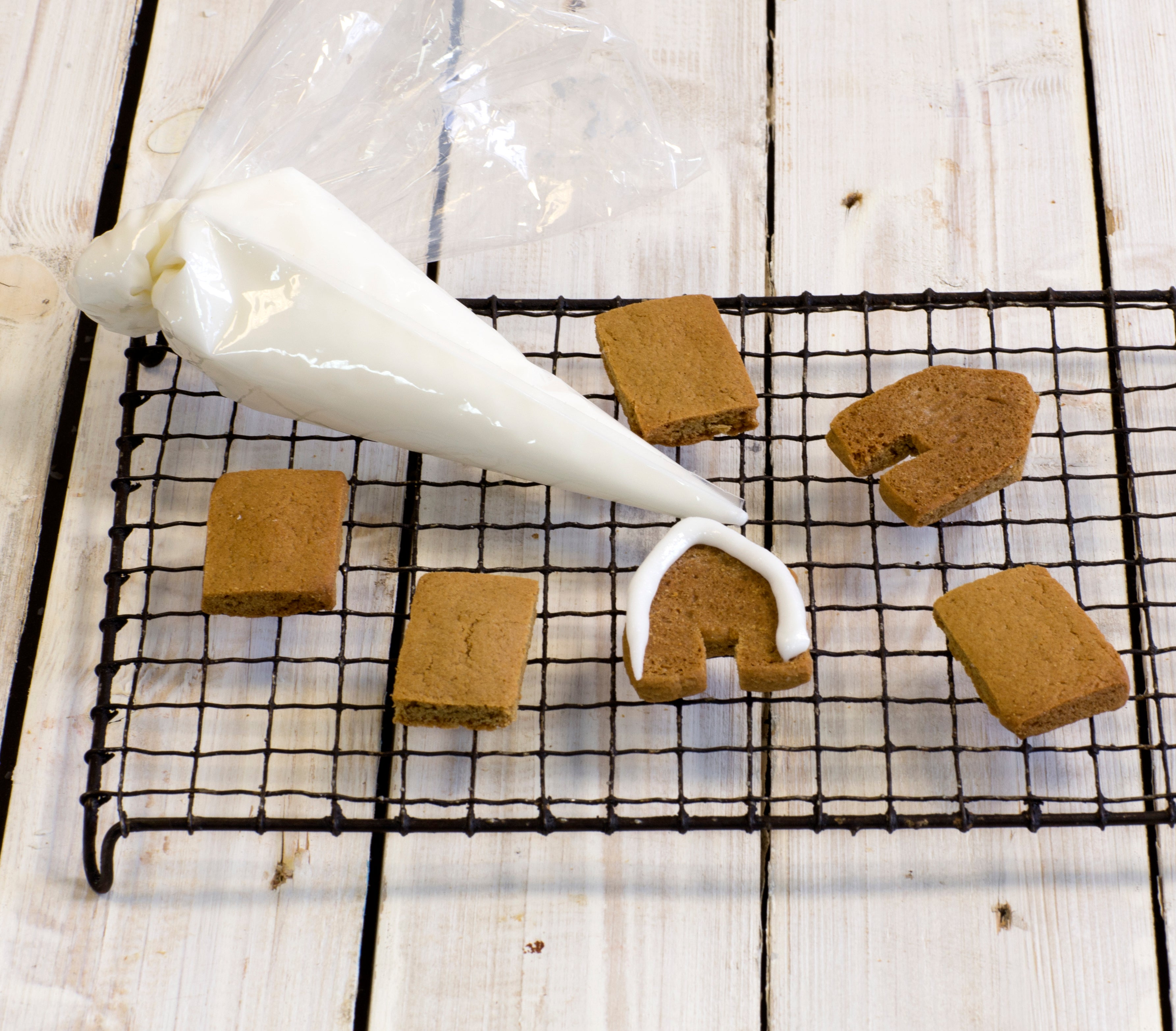 Baked gingerbread house shapes with icing bag