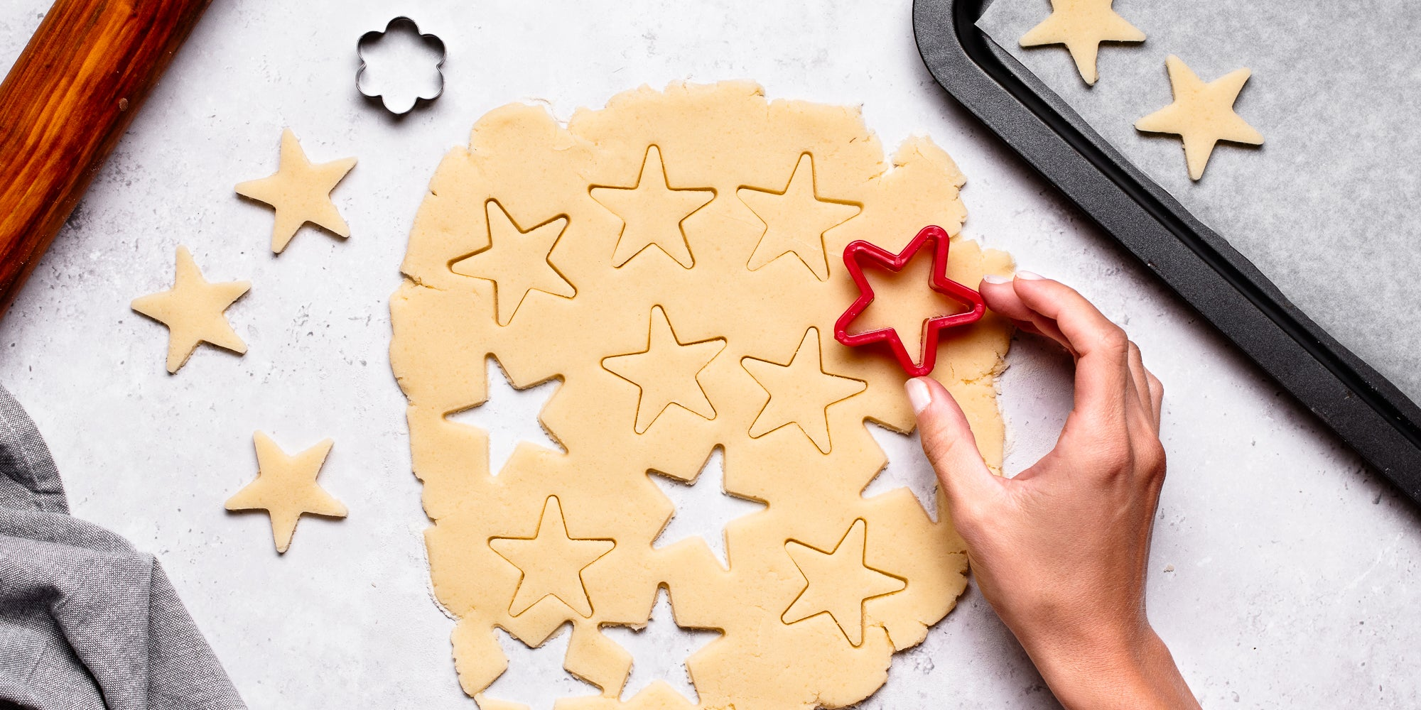 Top down view of a hand using a cookie cutter to cut out a star in vegan biscuit dough