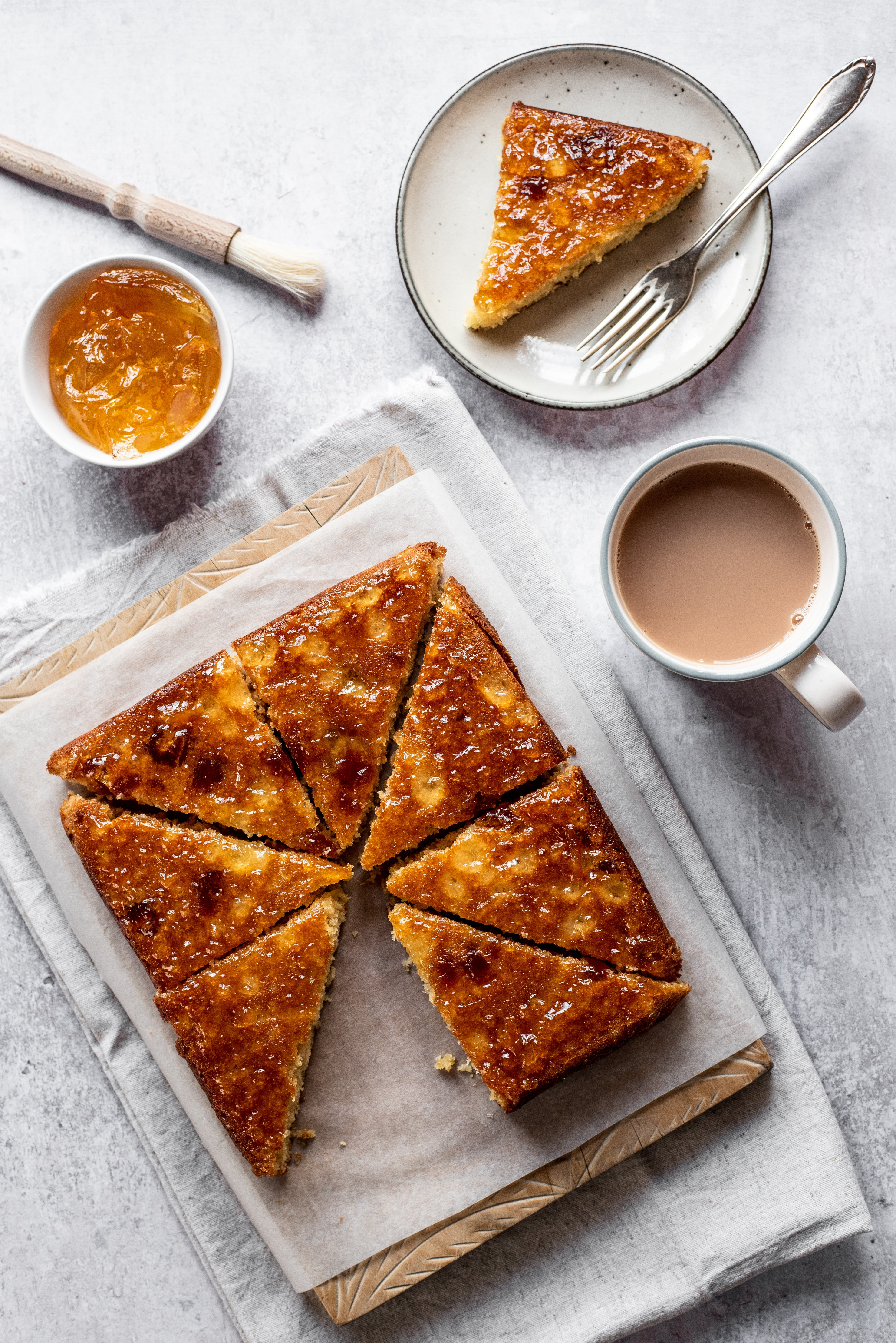 Top view of Marmalade Traybake sliced into pieces, on a sheet of baking paper, next to a cup of tea and a bowl of marmalade