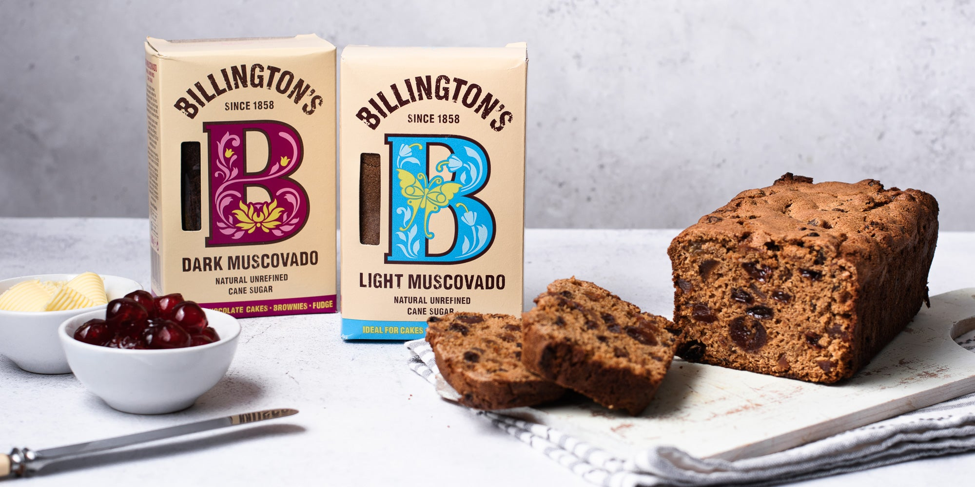 Billington's light and dark muscovado sugar next to a loaf of Irish Tea Brack sliced on a serving board