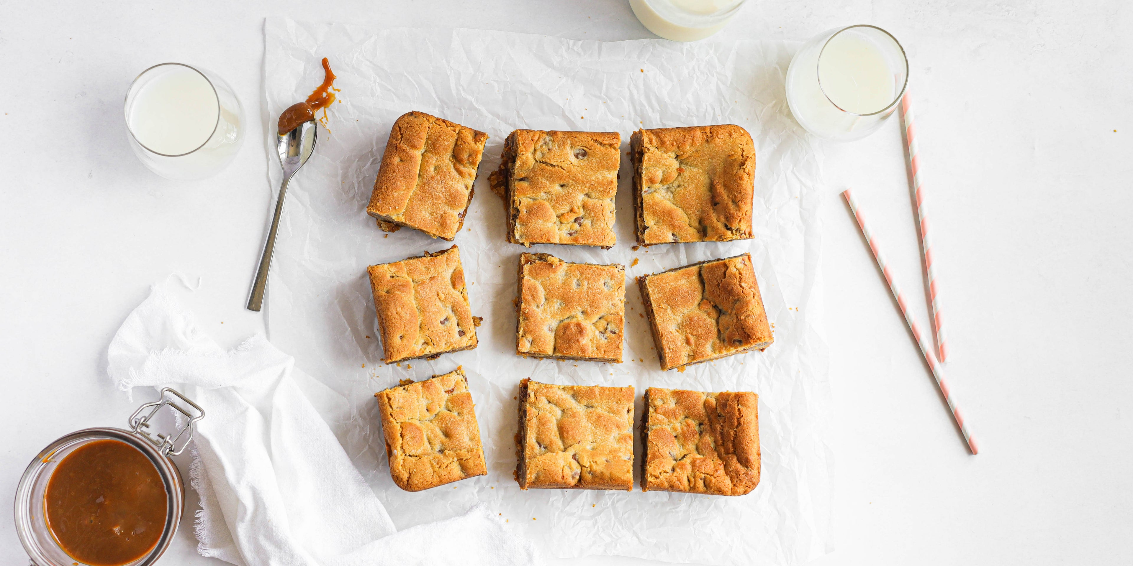Salted Caramel Cookie Traybake cut into squares and lay on baking paper, next to a spoon with caramel sauce and glasses of milk