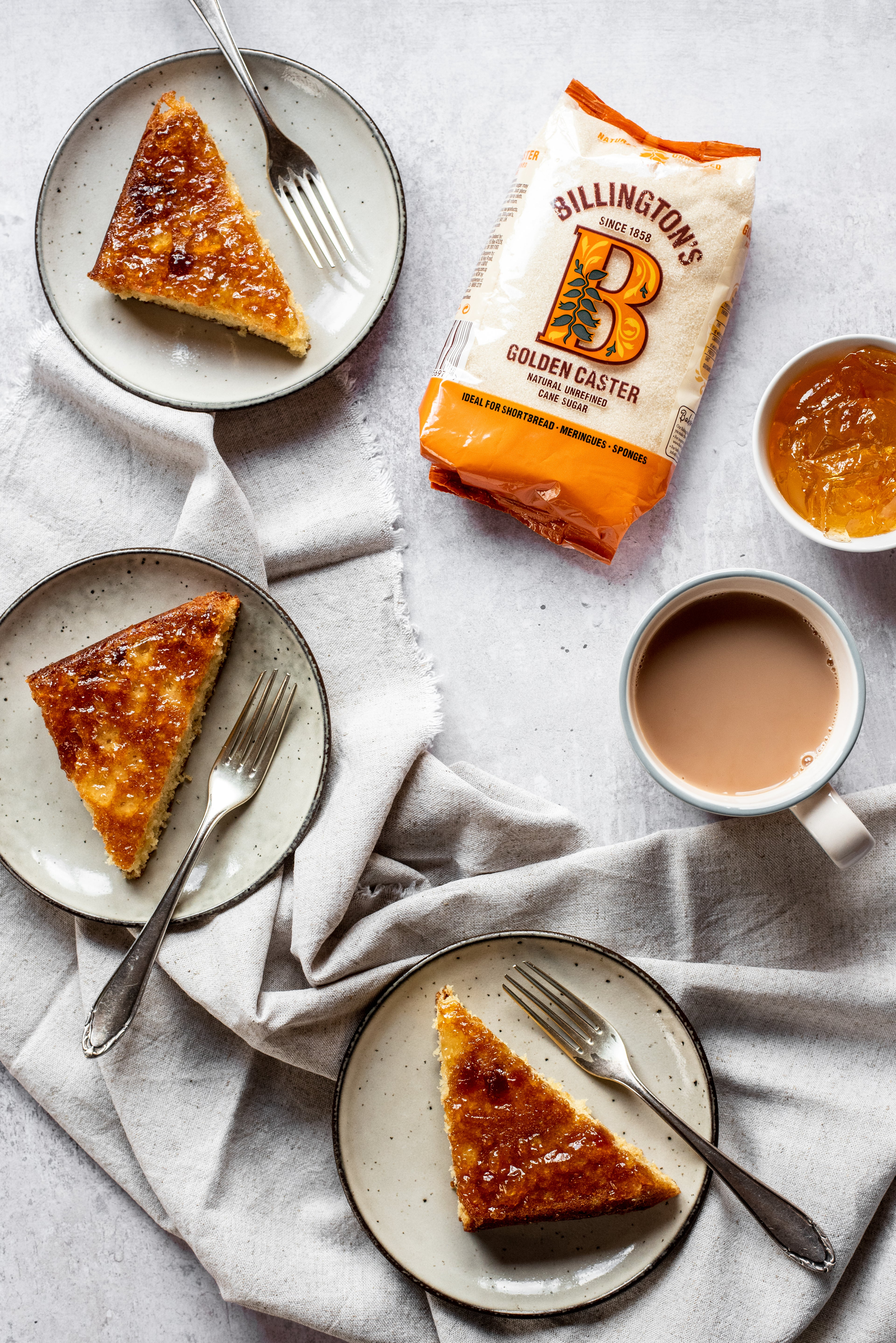 Slices of Marmalade Traybake on plates served with forks, next to a bag of Billington's Caster Sugar and a bowl of marmalade