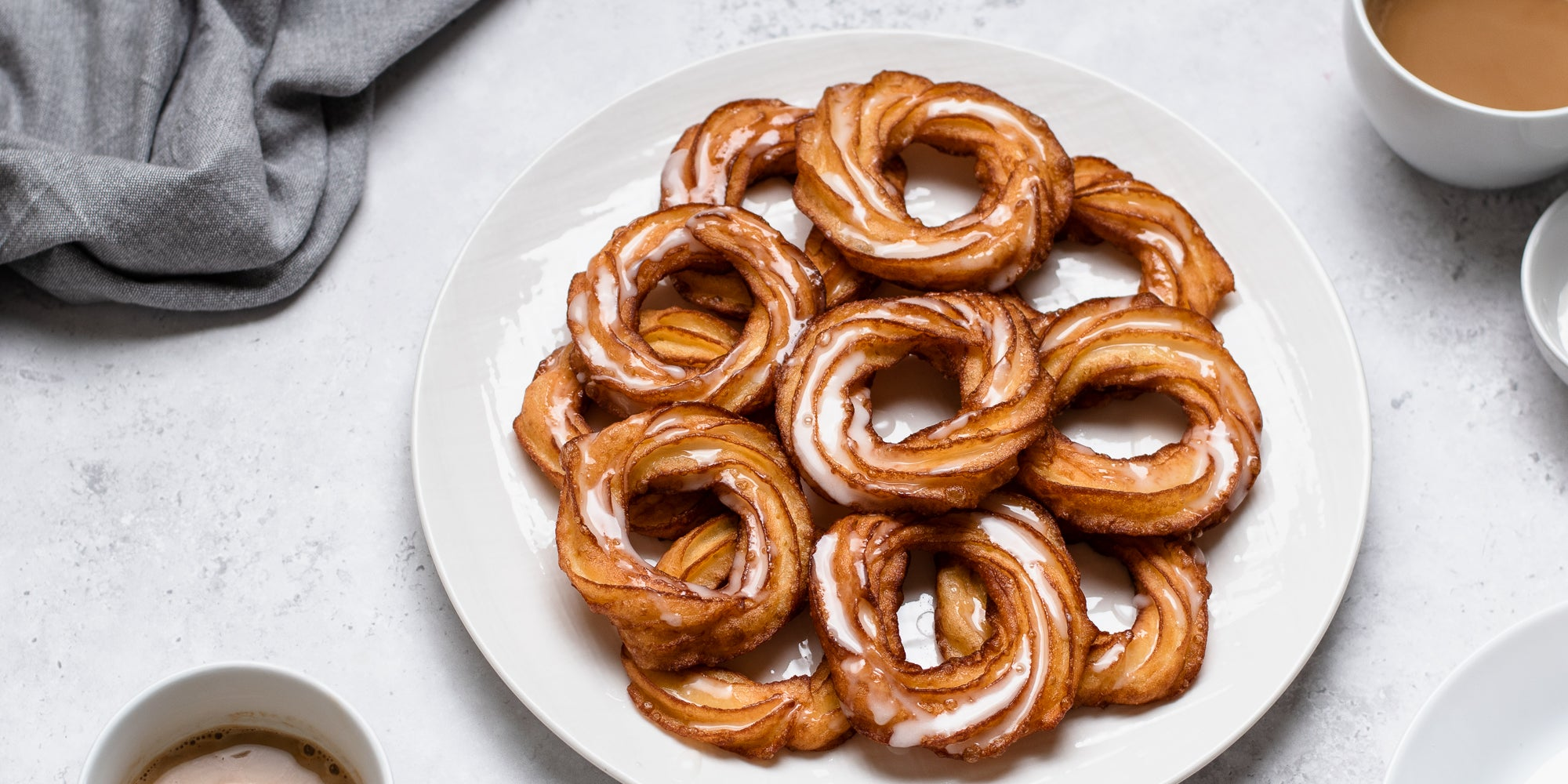 Close up of a plate of Apple Cider Crullers with icing and cinnamon sprinkled ontop