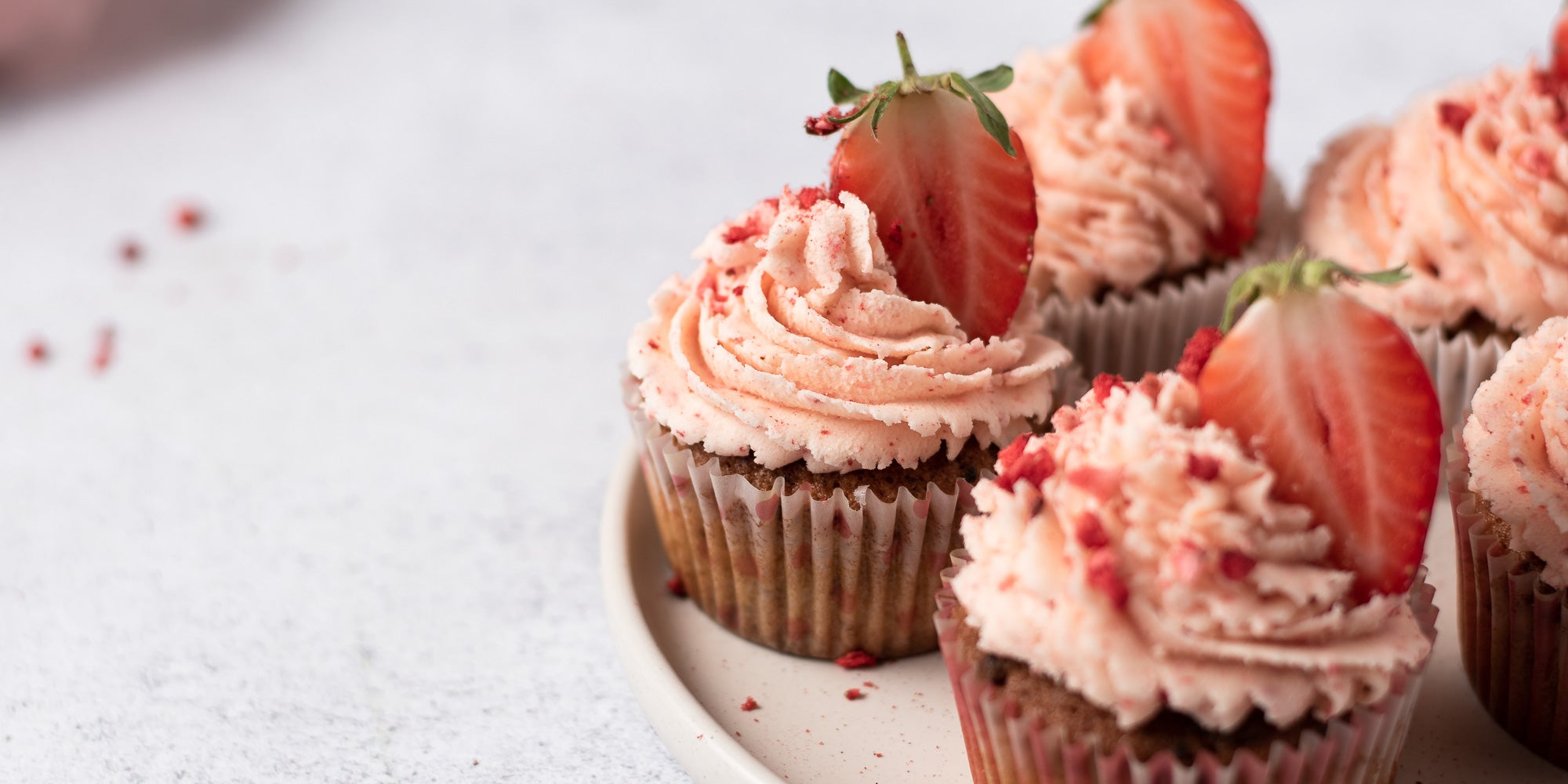 Strawberry cupcakes topped with strawberry buttercream and strawberries