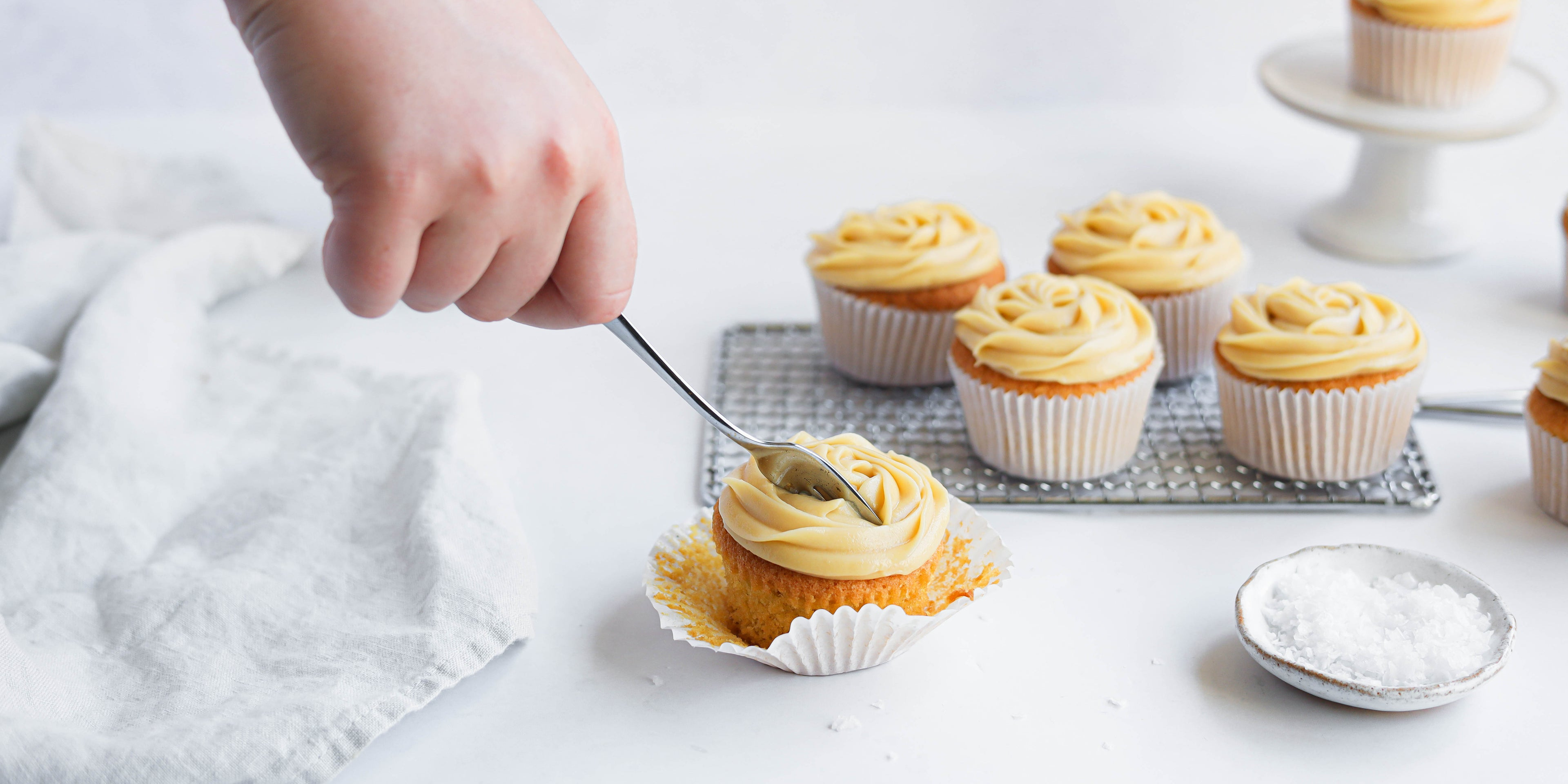 Salted Caramel Cupcakes with hand holding fork cutting into the cupcake buttercream, next to a small side dish of rock salt