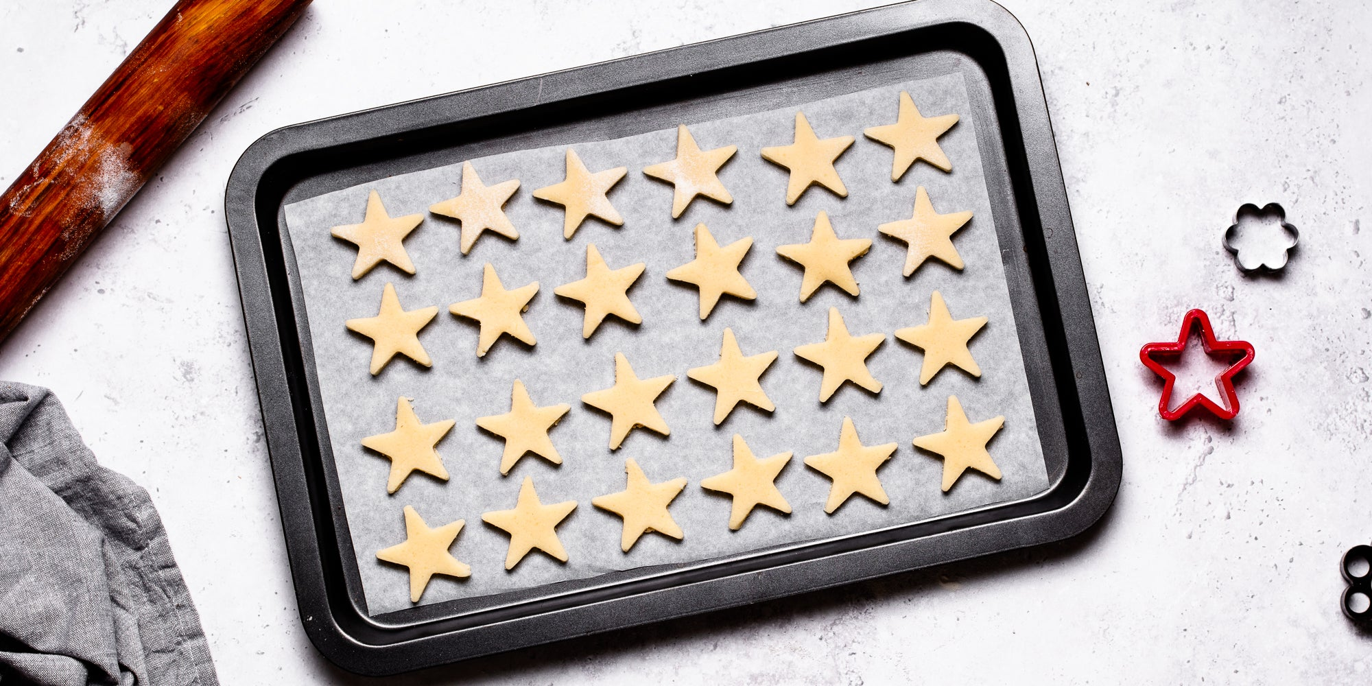 Top down view of vegan biscuit dough stars laid out on a baking tray