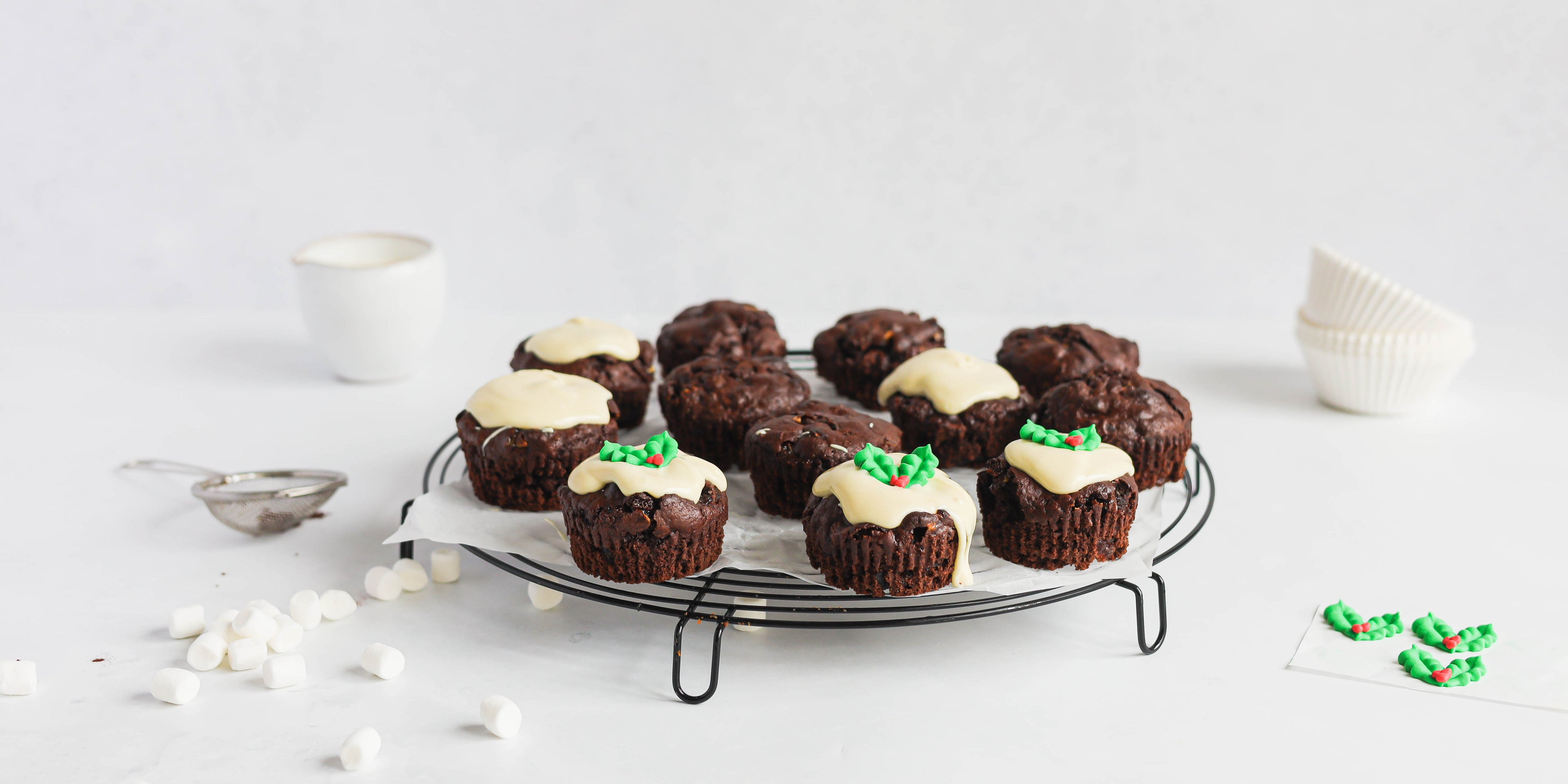 Mini Rocky Road Christmas Pudding Muffins on a wire rack, being decorated with white chocolate and holly.