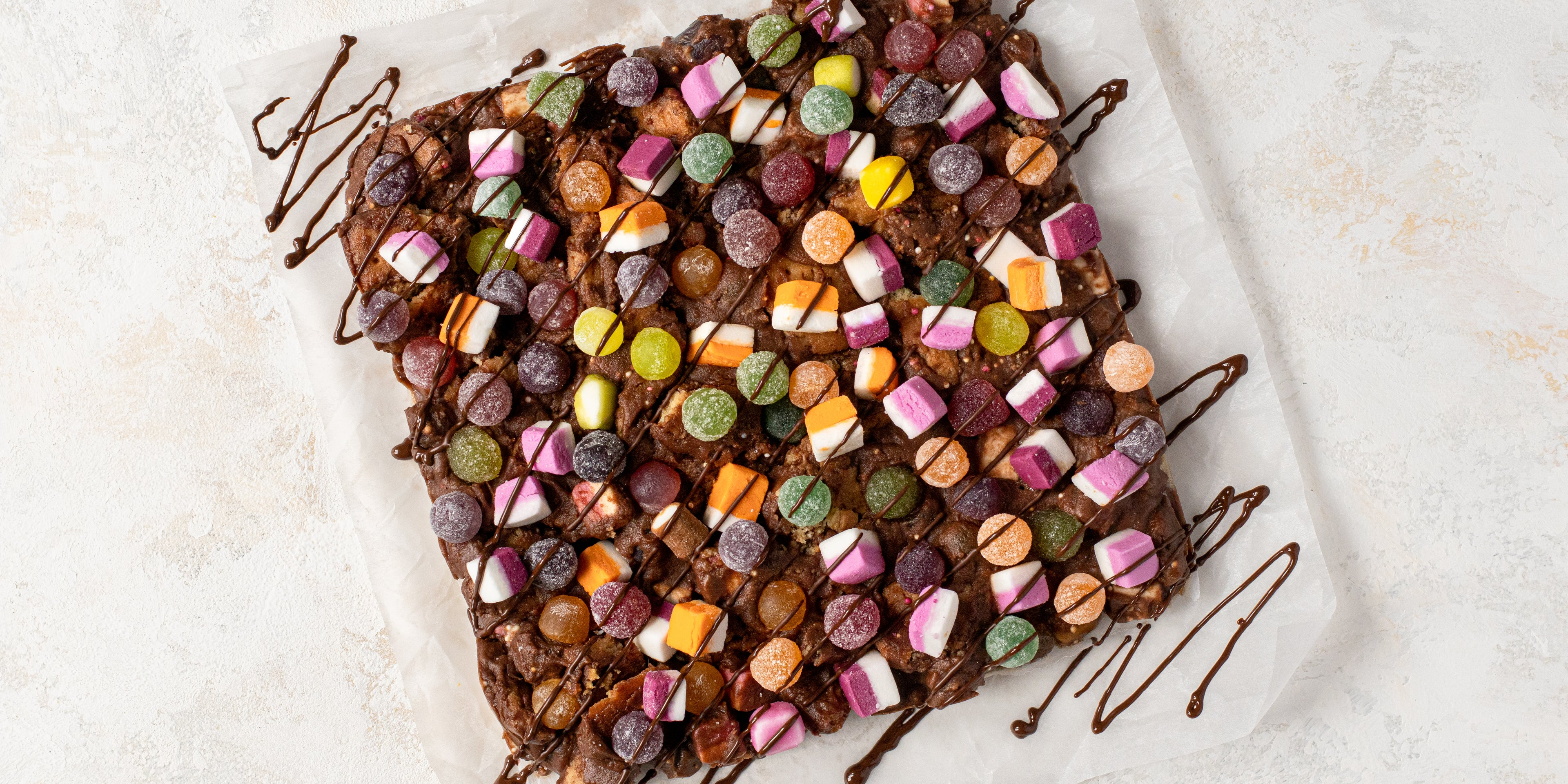 Top view of Sweetie Rocky Road on a sheet of baking paper, drizzled with chocolate