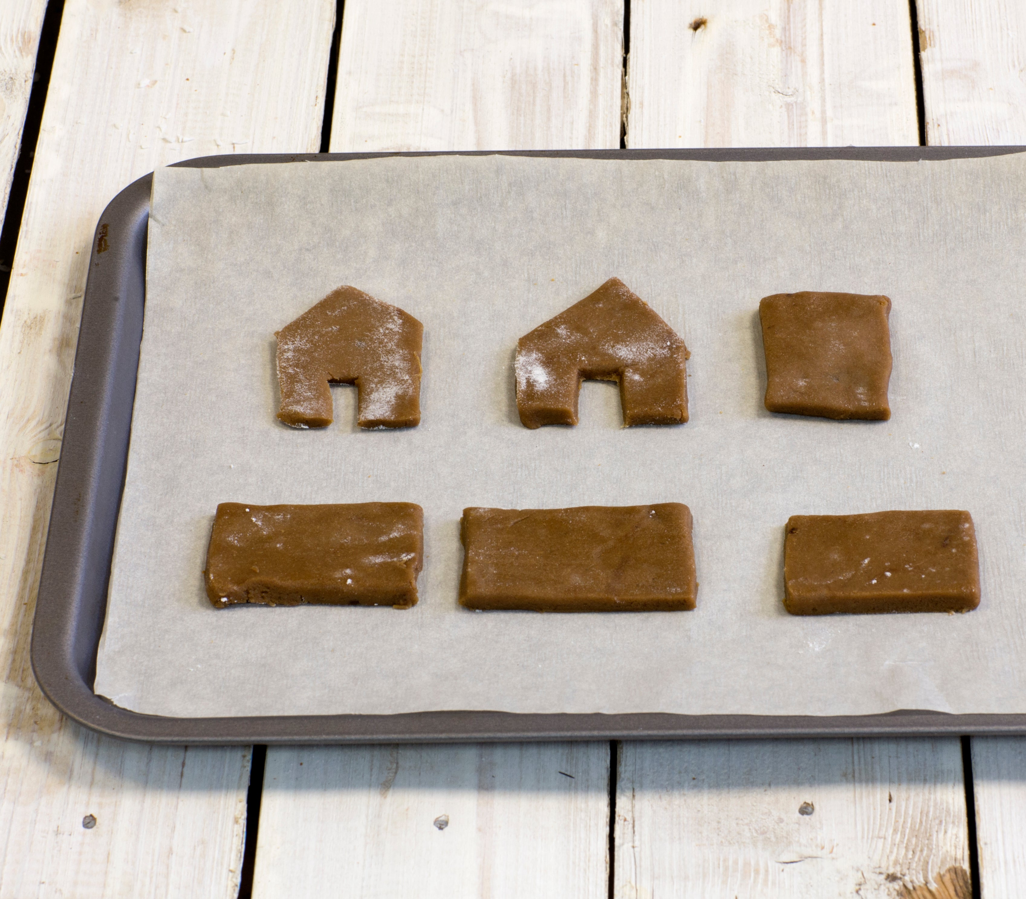 Gingerbread dough shapes laid out on baking tray