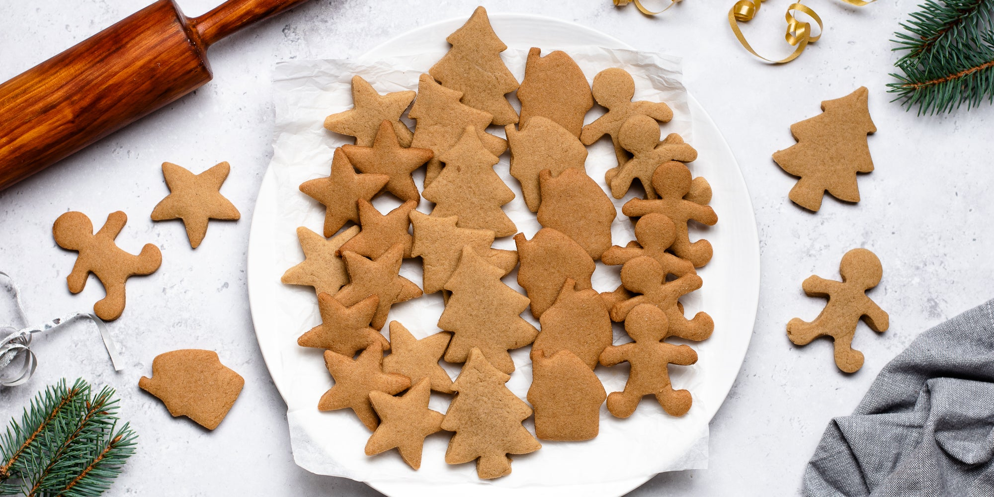 A batch of gingerbread cookies made from Gingerbread Dough, next to a rolling pin and pine leaves