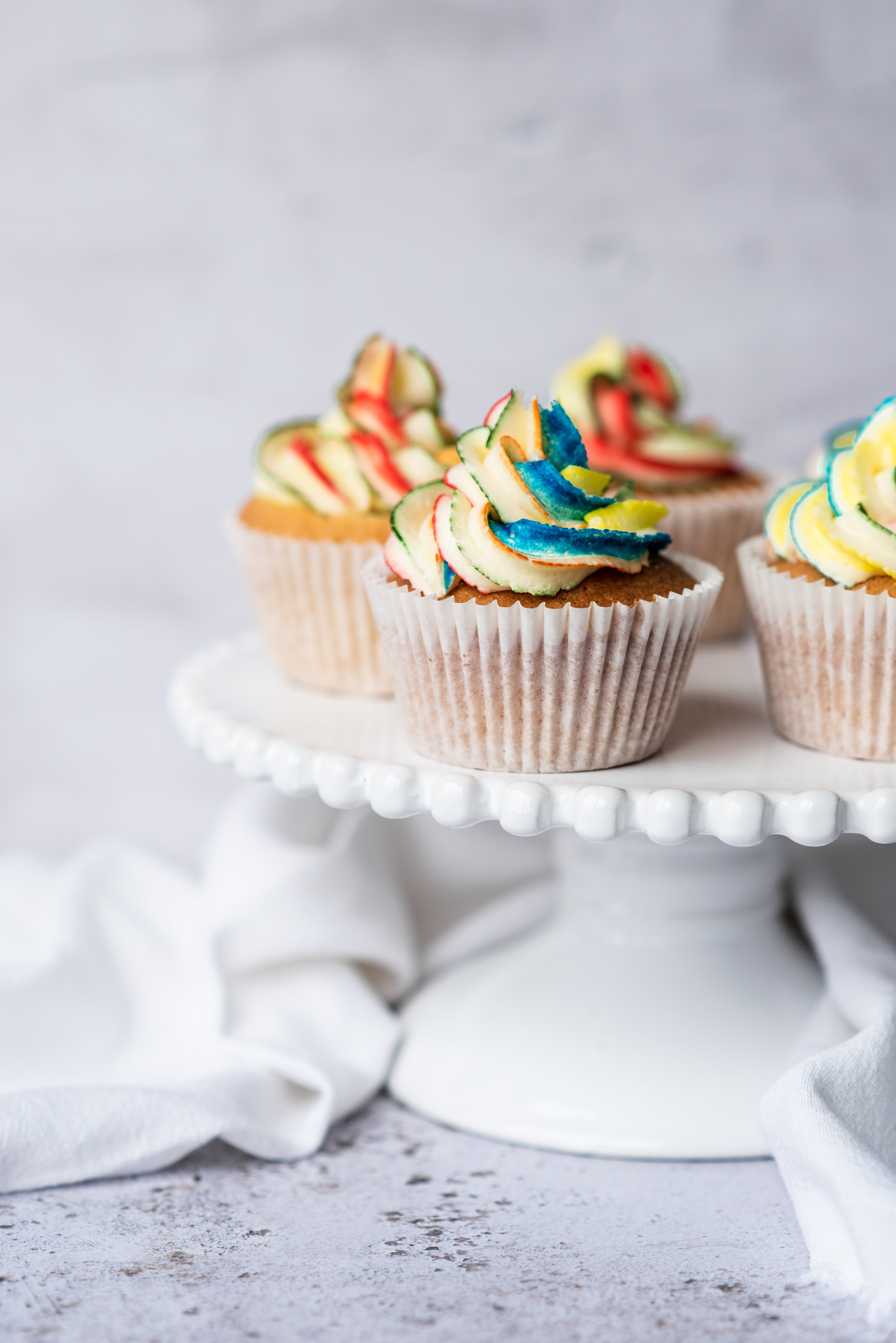 rainbow buttercream on a cupcake sitting on a cake stand