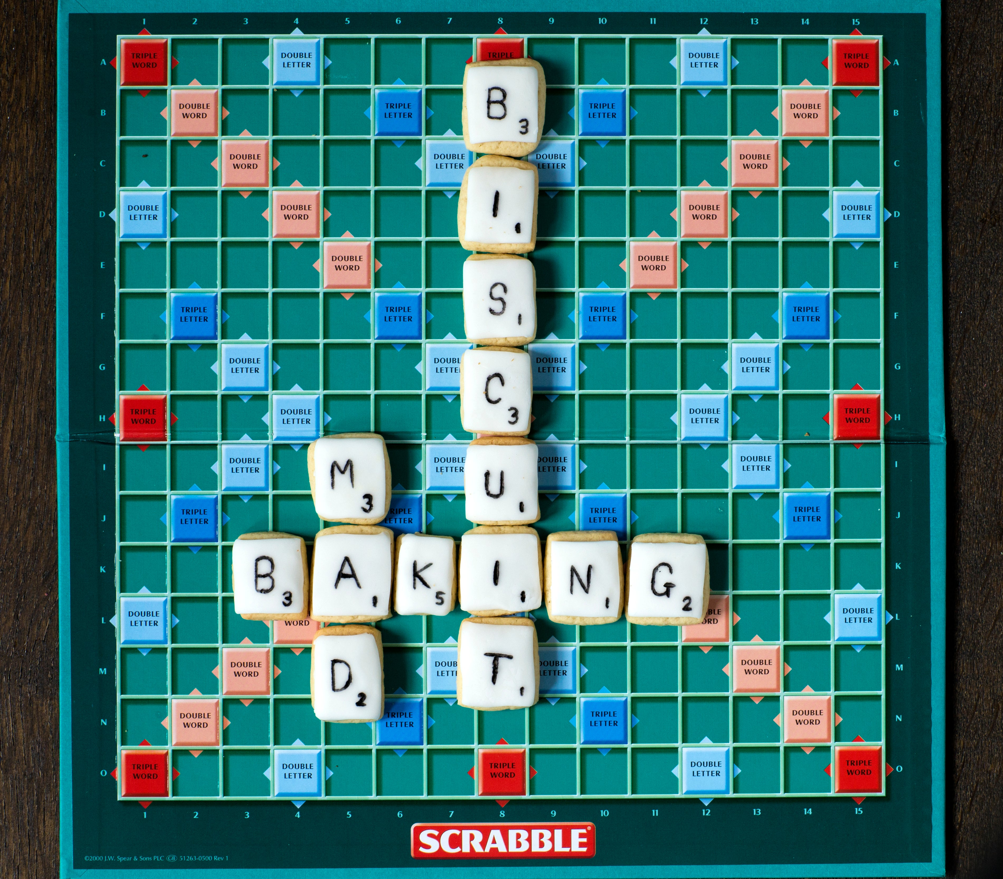 Overhead shot of a scrabble board with iced biscuits on