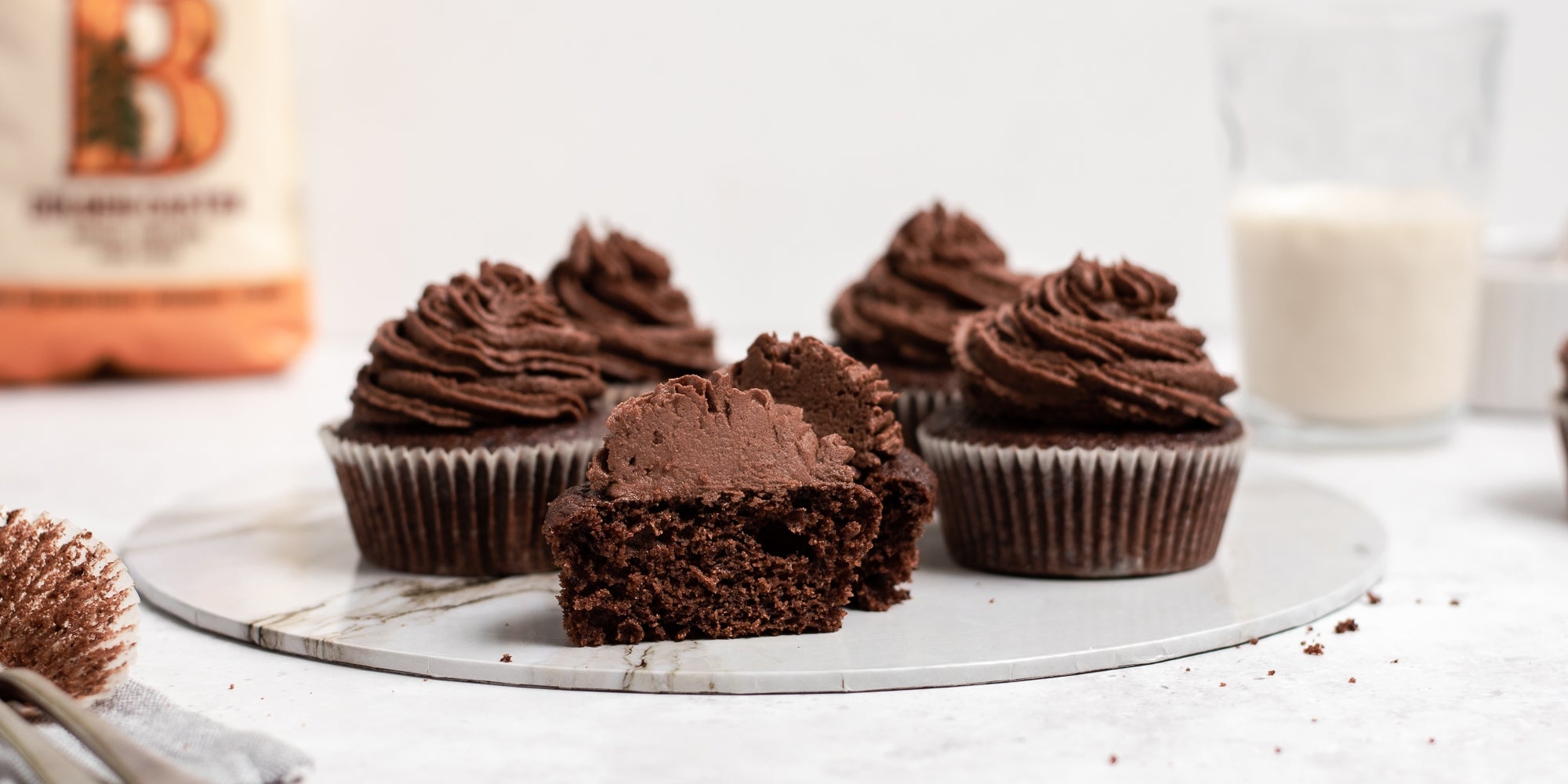 Close up of Vegan Chocolate Cupcakes on a marble board, with a cupcake cut in half showing the centre. A pack of Billington's Golden Caster sugar in the background