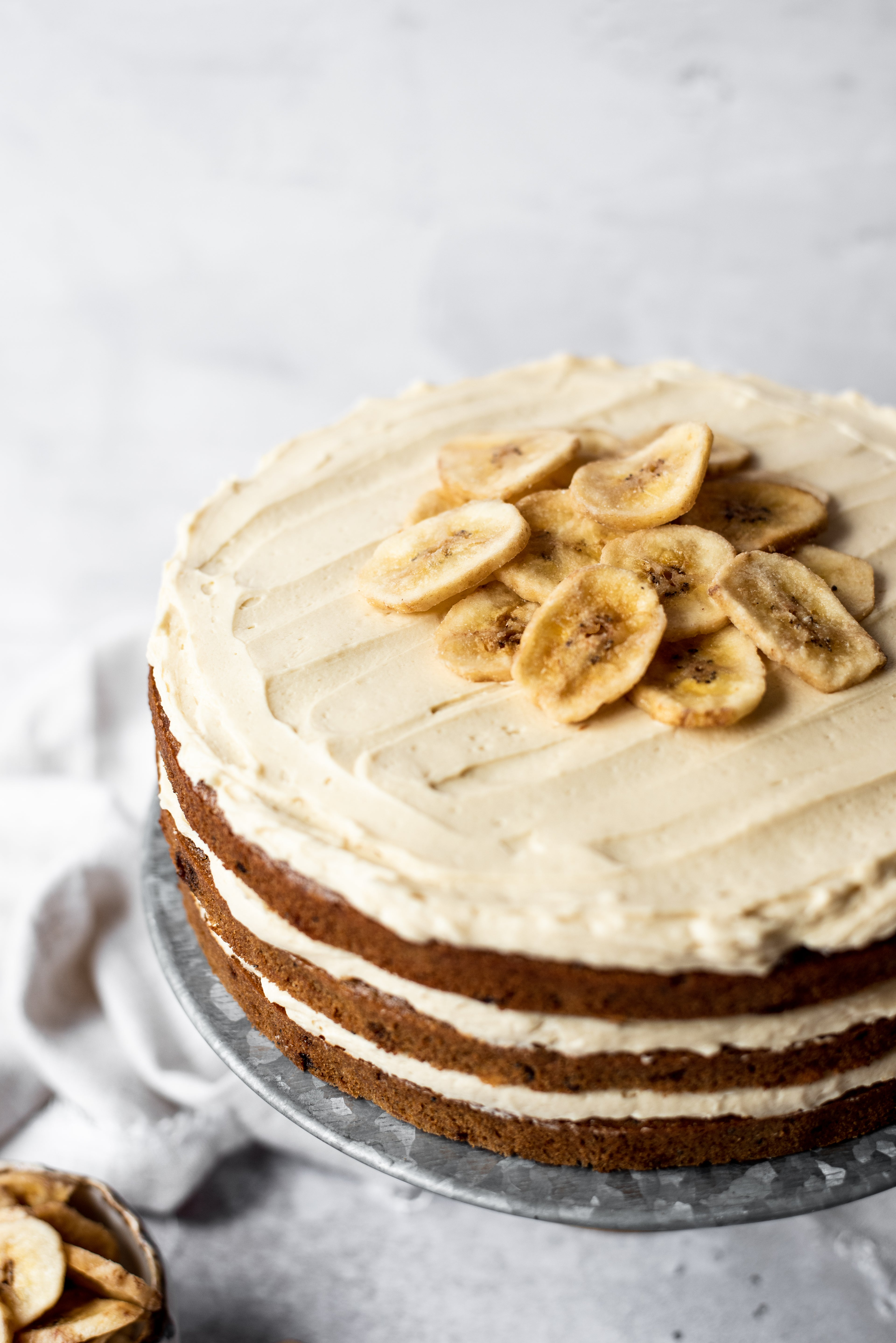 Close up of banana layer cake with 3 layers on cake stand topped with buttercream and banana chips