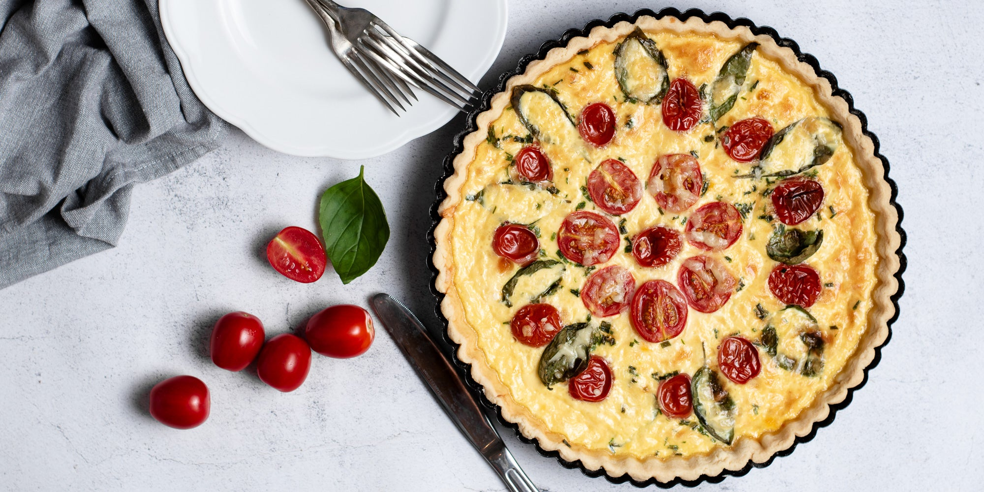 Flay lay view of a Cheese & Tomato Quiche with two forks ready to serve.