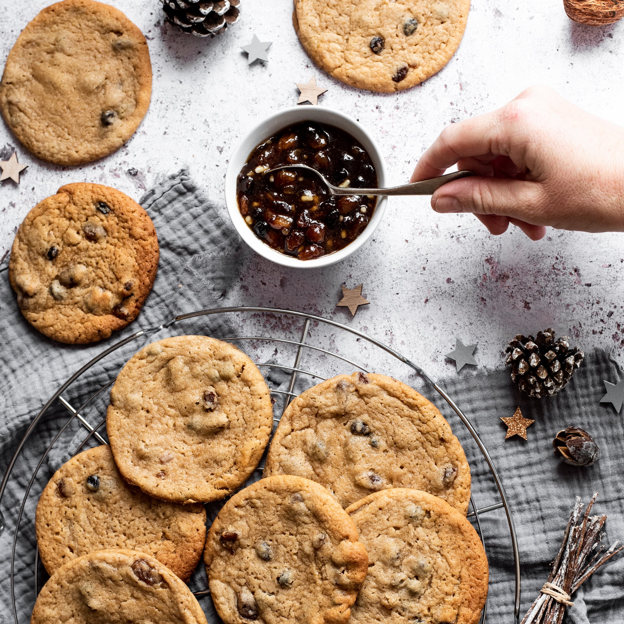 Mince pie cookies on a circular cooling rack, a hand spooning mincemeat out of a small bowl
