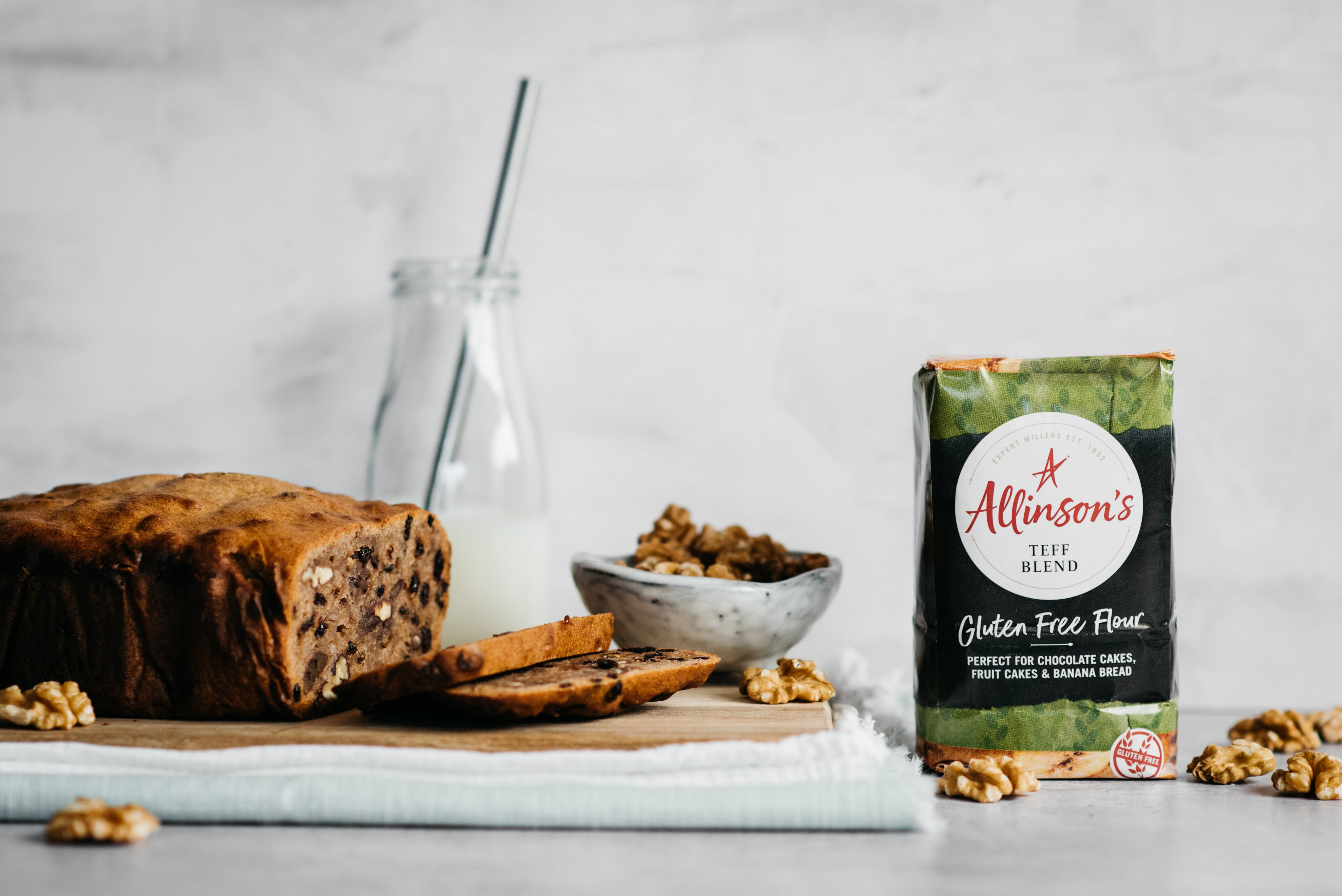 Banana bread, slice cut infront, bowl of walnuts, flour pack and milk bottle in background