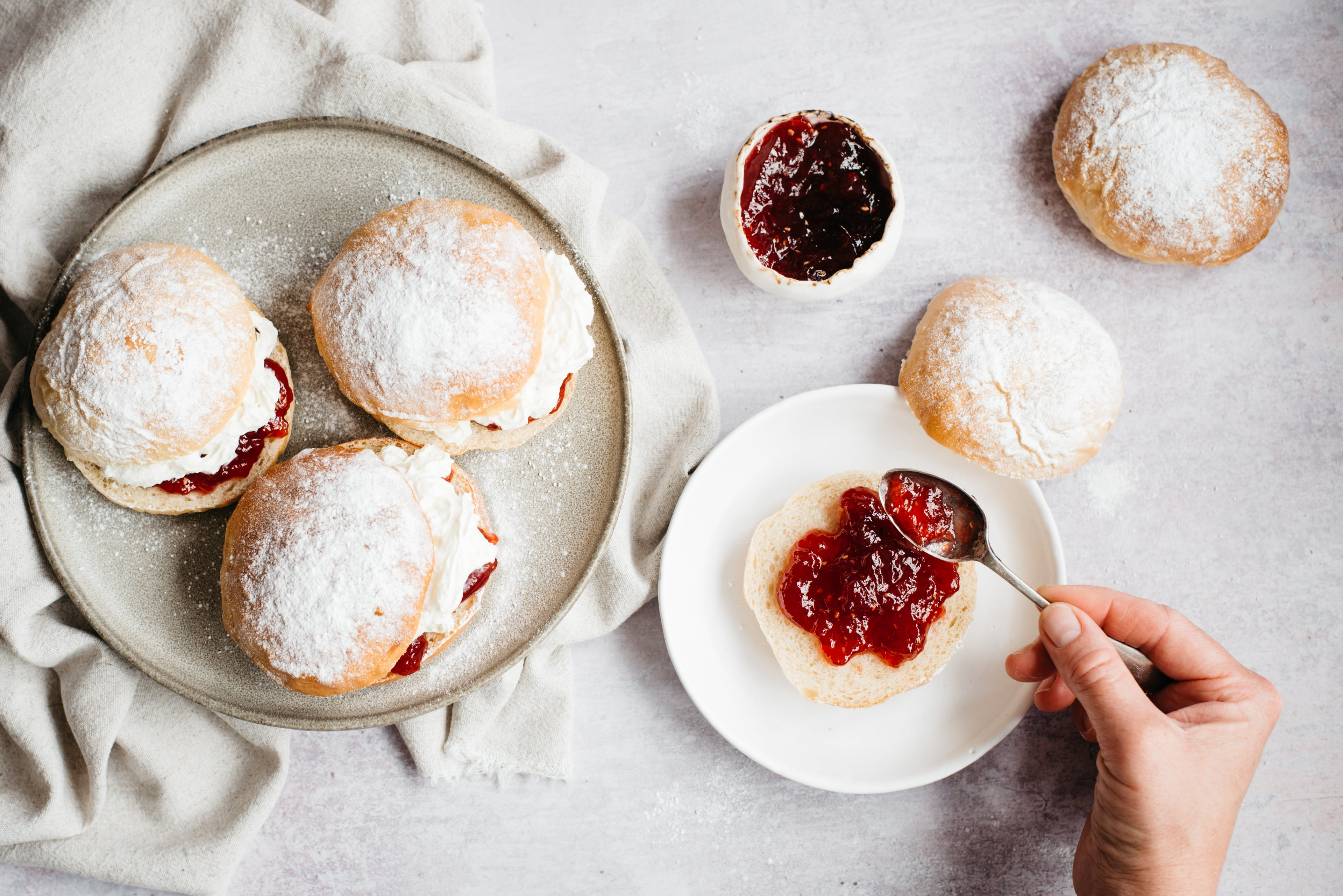 Top view of a plate of Devonshire Splits with a hand spreading jam over half of a Devonshire Split with a spoon, next to a bowl of jam