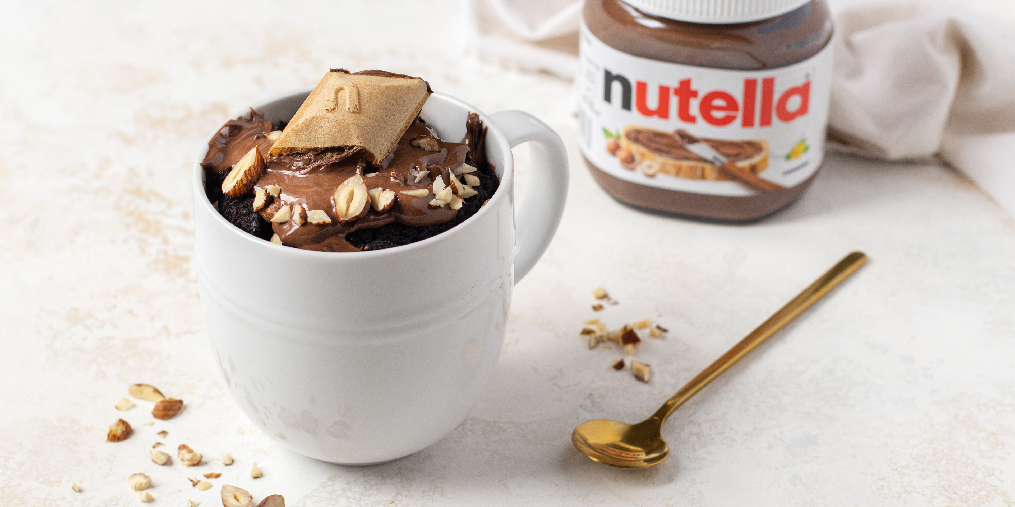 Chocolate Mug Cake customised with Nutella, with Nutella spread on top and sprinkled with hazelnuts. In the background there is a jar of Nutella next to a spoon
