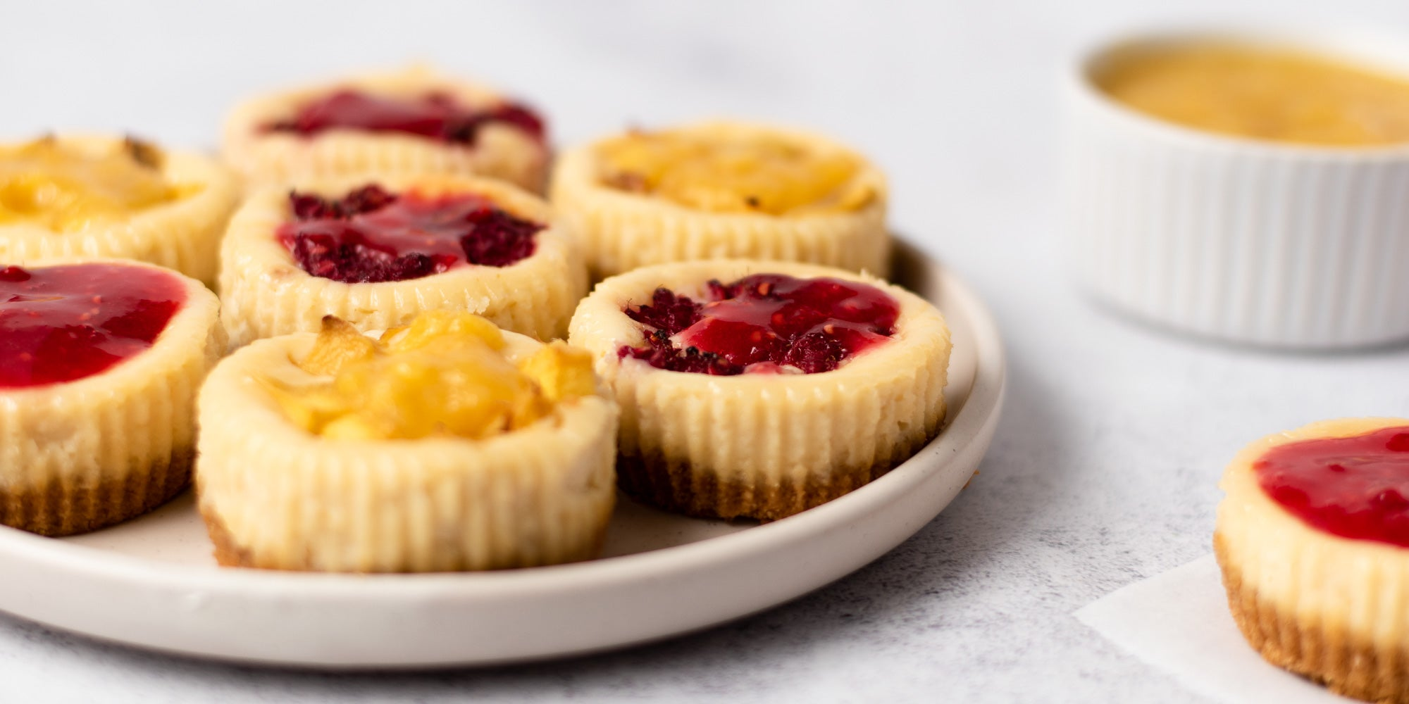 Plate of mini cheesecakes topped with fruit