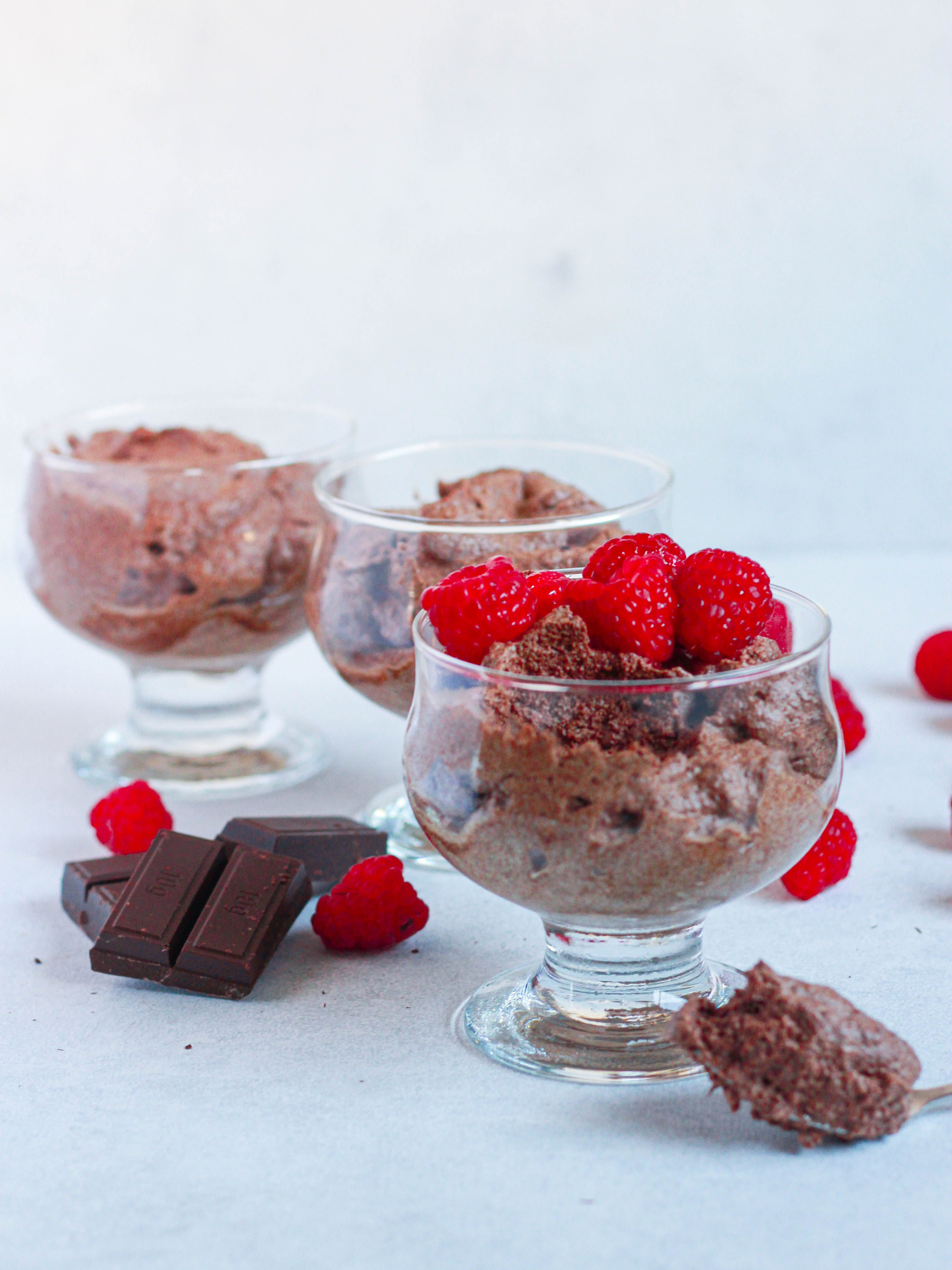 3 bowls of chocolate mousse, topped with raspberries and chocolate chunks