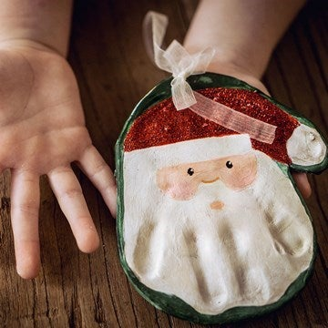 Hand print salt dough shape decorated to look like Santa